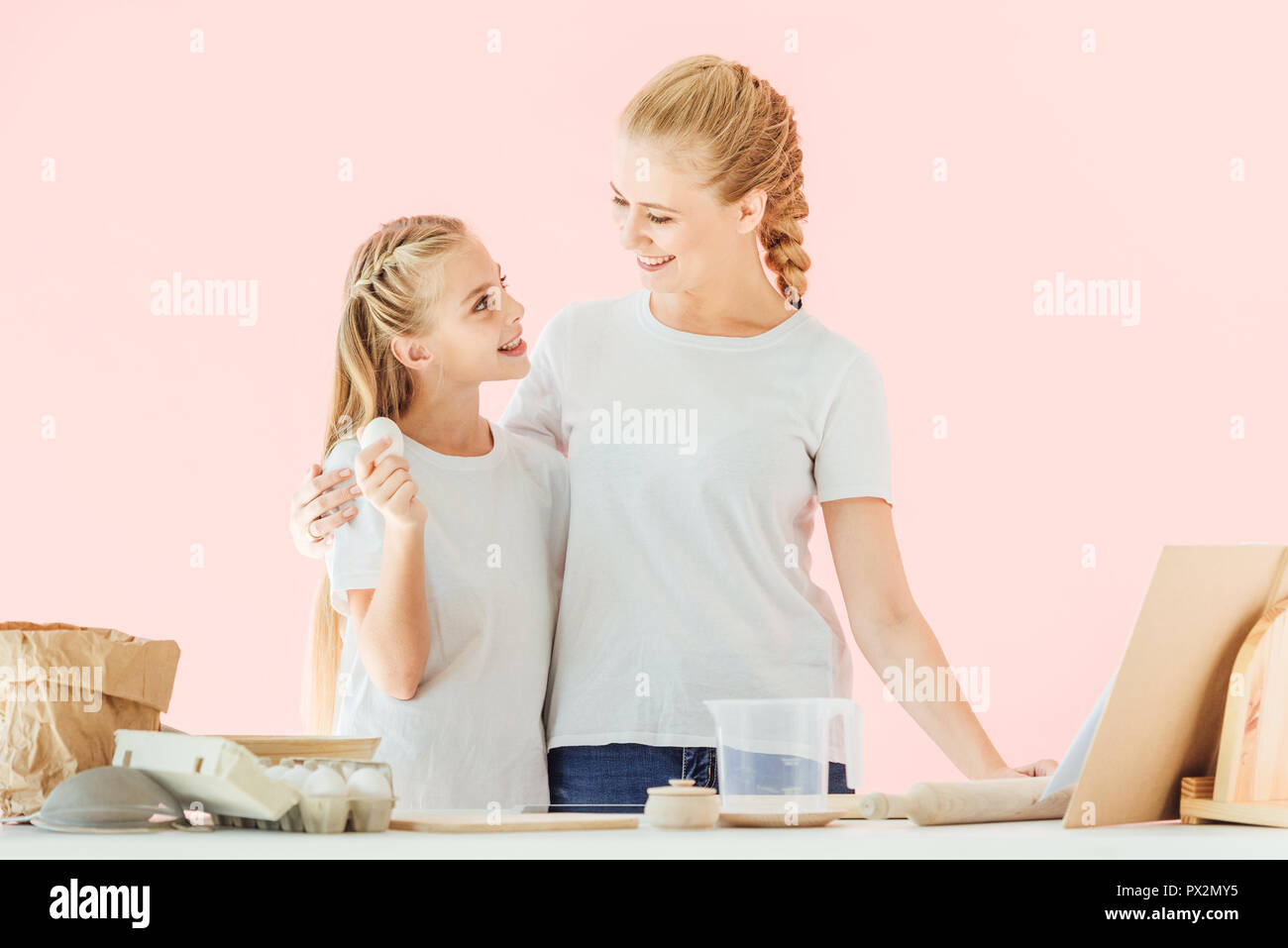 young mother and adorable little daughter in white t-shirts looking at each other during cooking isolated on pink - Stock Image
