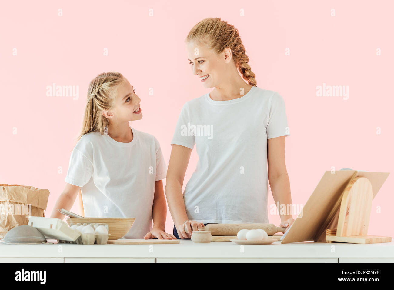 smiling mother and daughter in white t-shirts looking at each other while cooking together isolated on pink - Stock Image