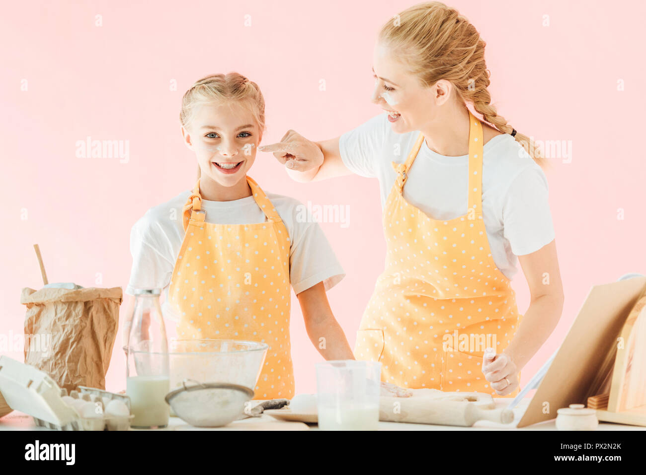 smiling mother and daughter with flour on faces cooking together isolated on pink - Stock Image