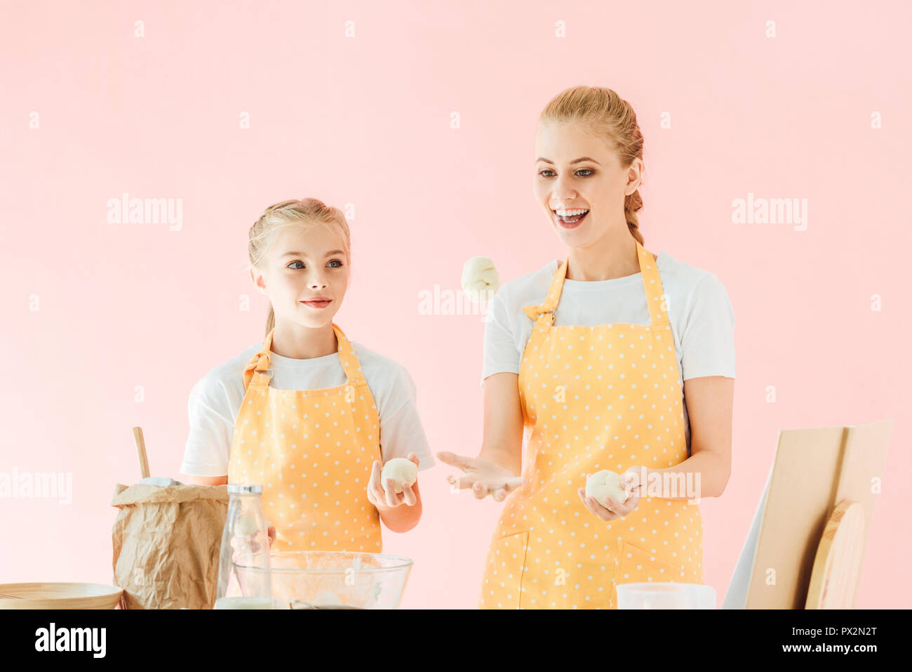 smiling mother and daughter juggling with dough pieces while cooking isolated on pink - Stock Image