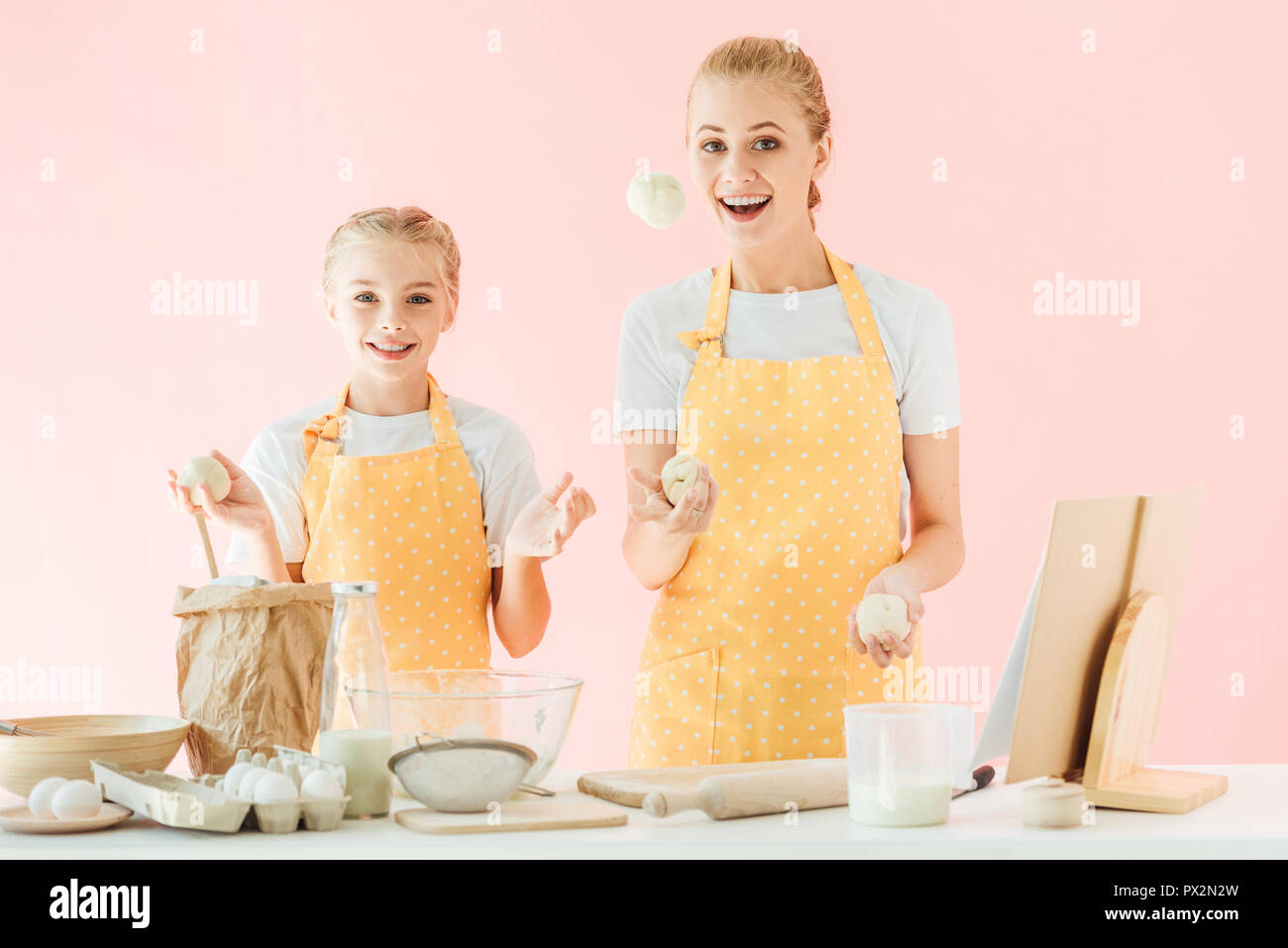 happy mother and daughter juggling with dough pieces while cooking isolated on pink - Stock Image