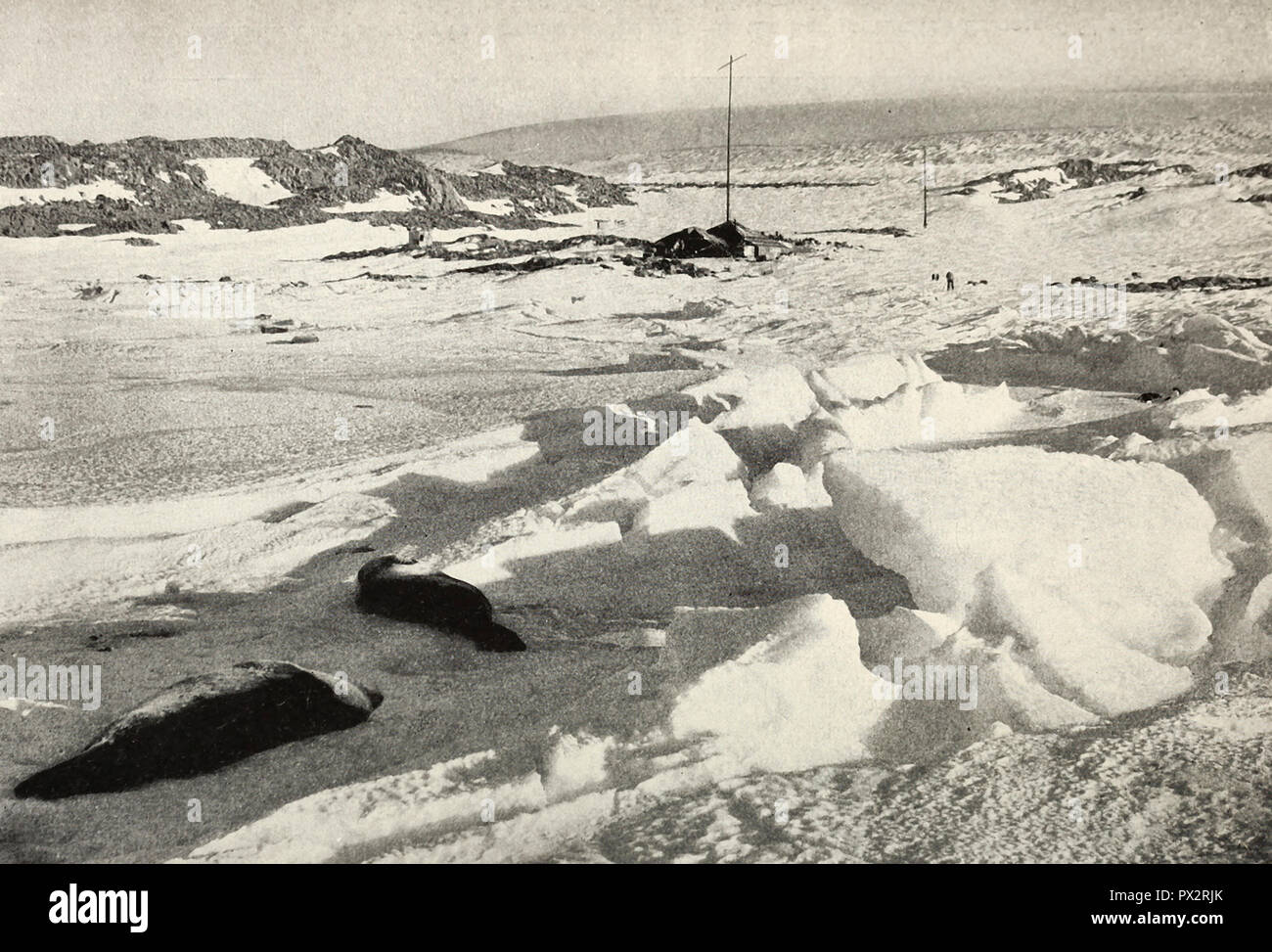 WInter Quarters, Adelie Land. The hut lies at the foot of the wireless mast near the center. In the background the slopes rise to a plateau. This was the way by which sledging parties made their way to the interior. Antarctica, circa 1910 - Stock Image