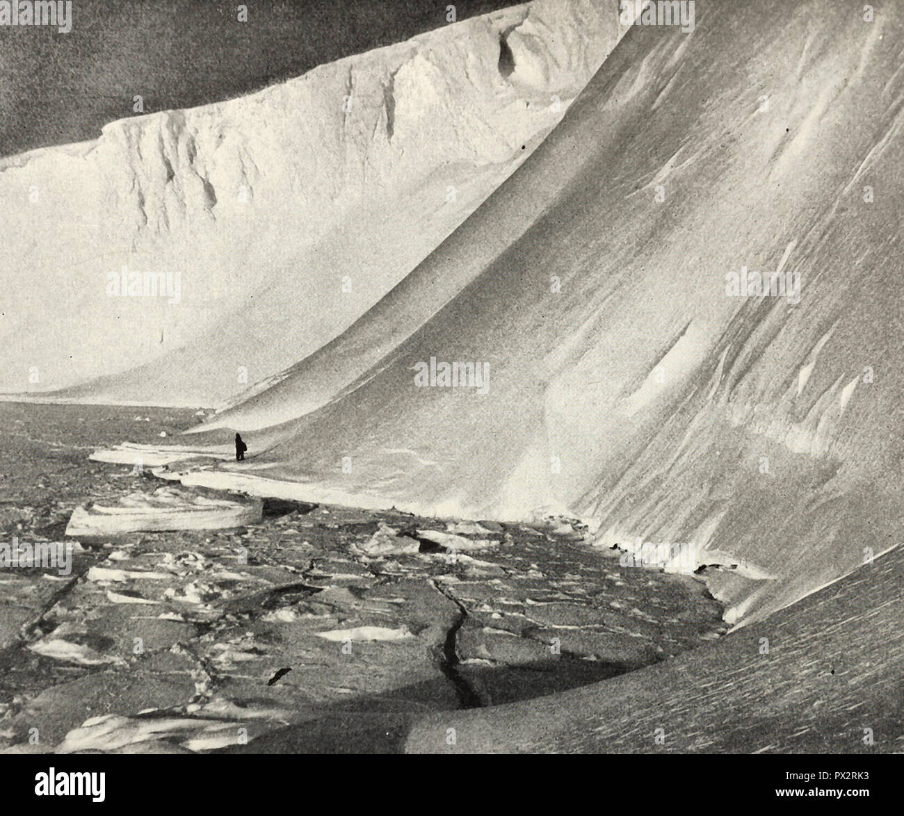Man filled with awe as he stands beneath mighty ice walls, which tower one hundred and eighty feet above him, Antarctica, circa 1910 - Stock Image