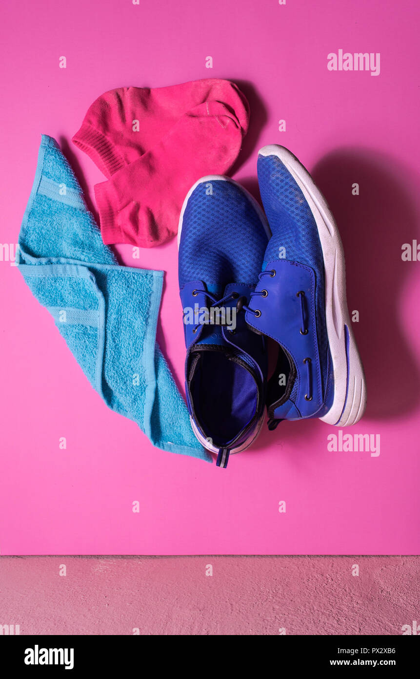 blue sports shoes on an isolated pink background, blue towel for sports accessory, fitness concept. . shot from above, trendy contrasting colors - Stock Image