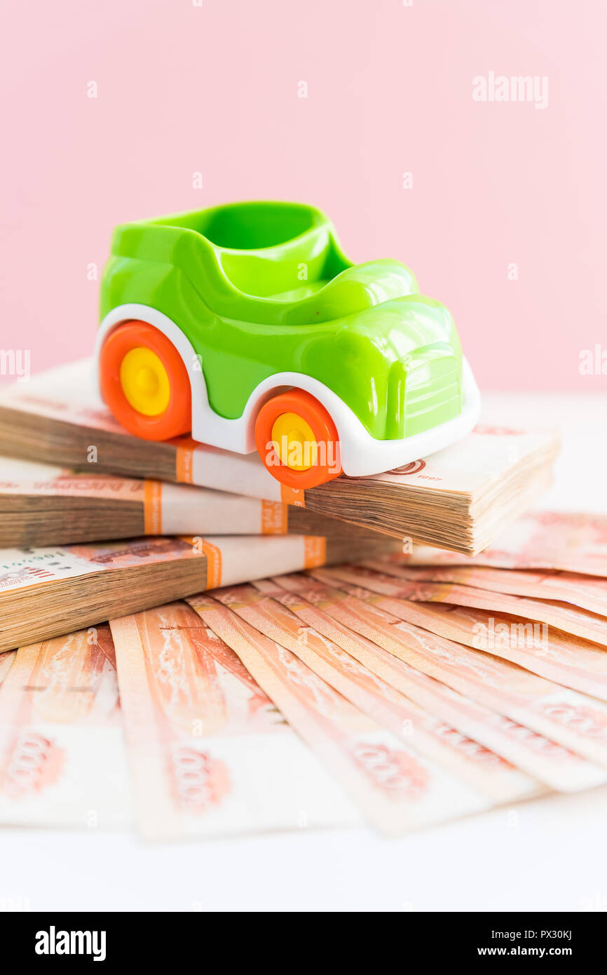 Car and money. Concept for buying, renting, insurance, fuel, service and repair costs.Saving money to buy a dream car. green toy car and russian money, banknotes.Copy space - Stock Image