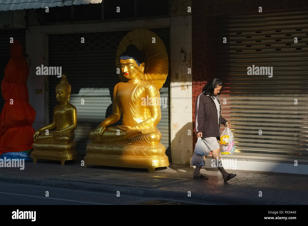 A woman, in early morning sunlight, passing Buddha statues outside a factory and outlet for religious objects in Bamrung Muang Rd., Bangkok, Thailand - Stock Image