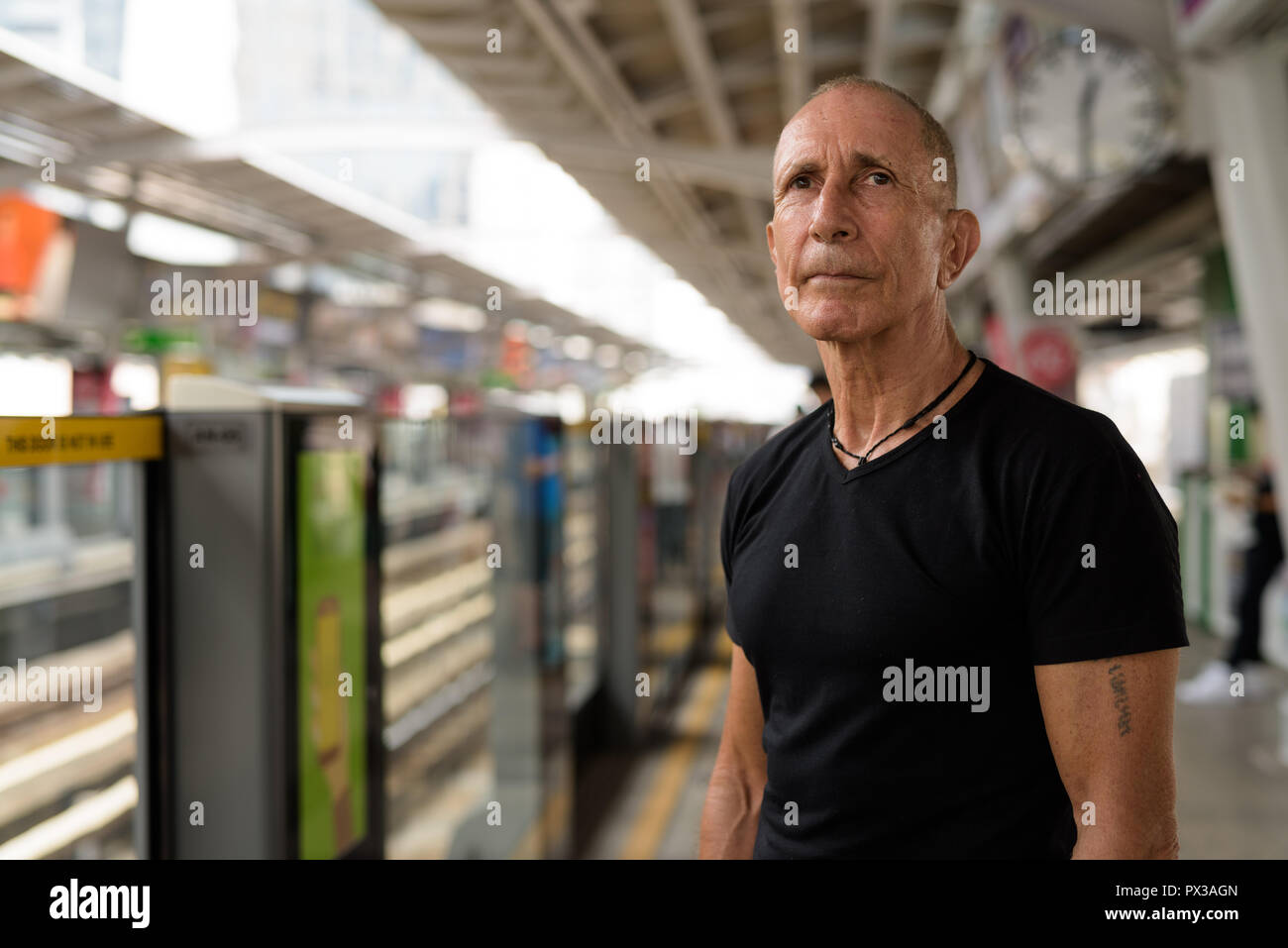 Bald senior tourist man waiting for the train at BTS sky train s - Stock Image
