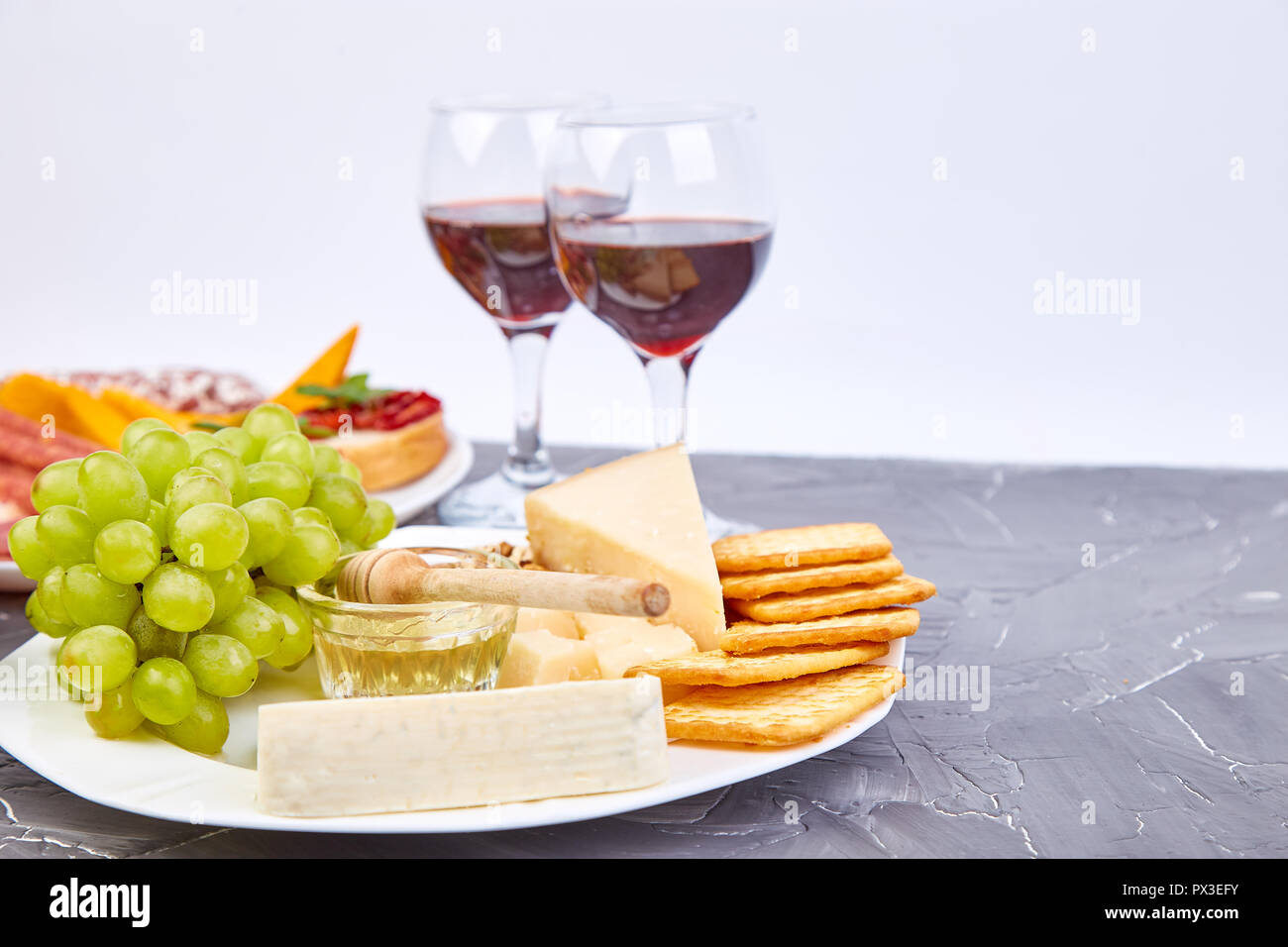 Cheese Plate Variety And Wine In Glasses On Grunge Grey Background Italian Antipasti Wine Snacks Set Copy Space Stock Photo Alamy