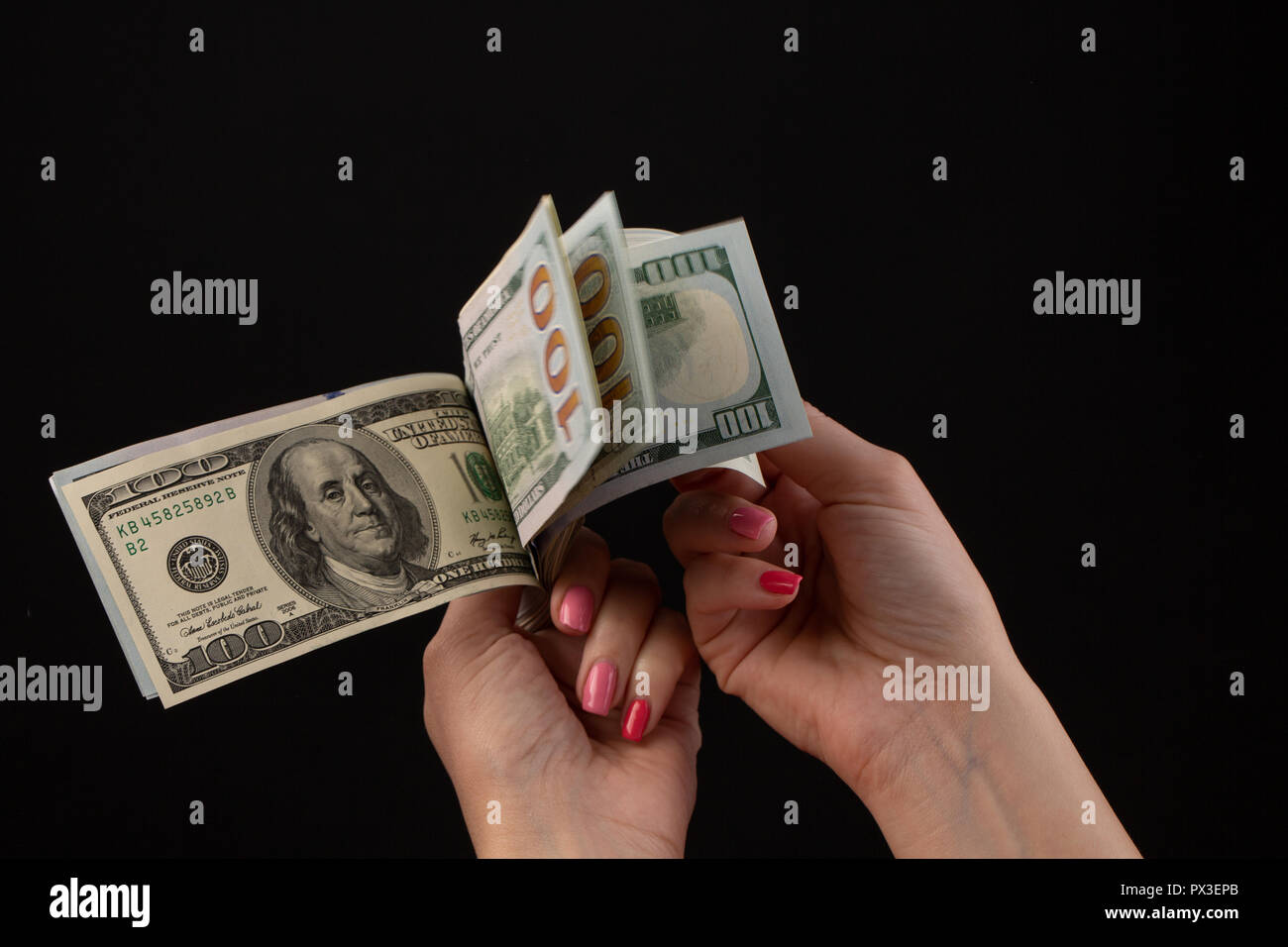 Hand giving money, United States Dollars or USD. Hands holding Banknotes. Hands holding a dollar 100 bill on black background - Stock Image