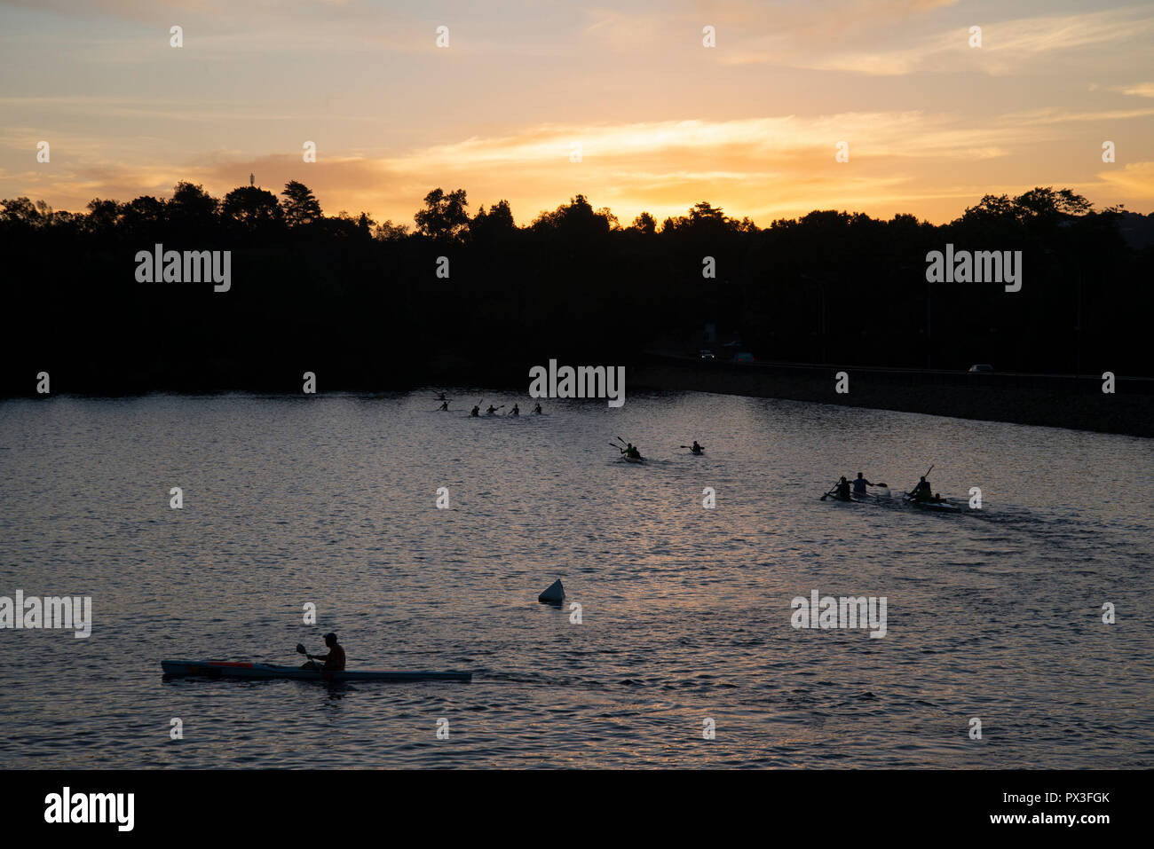 Johannesburg, South Africa, 18 October, 2018. Paddlers are seen on Emmarentia Dam as dusk settles over Johannesburg. The dam is located a few kilometers from the city center. It's a popular destination for athletes and families and is used for paddling canoes, sailing small boats and rowing. Credit: Eva-Lotta Jansson/Alamy Live News - Stock Image