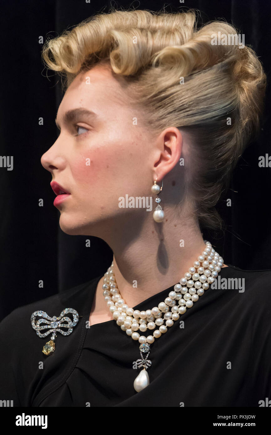 """London, UK.  19 October 2018. A model wears Marie Antoinette's jewels (L to R) diamond brooch, second half of the 18th century (Est. USD 50k-80k), natural pearl and diamond necklace three rows of 116 graduated pearls (Est USD200k-300k), natural pearl and diamond necklace (Est USD40k-70k), """"Queen Marie Antoinette's Pearl"""", natural pearl and diamond pendant 18th century set (Est USD1m-2m), and pair of natural and pearl diamond pendant earrings, late 18th century (Est USD200k-300k). Credit: Stephen Chung/Alamy Live News Stock Photo"""