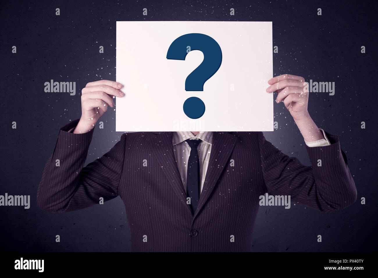 Young businessman hiding behind a question mark drawn on paper  - Stock Image
