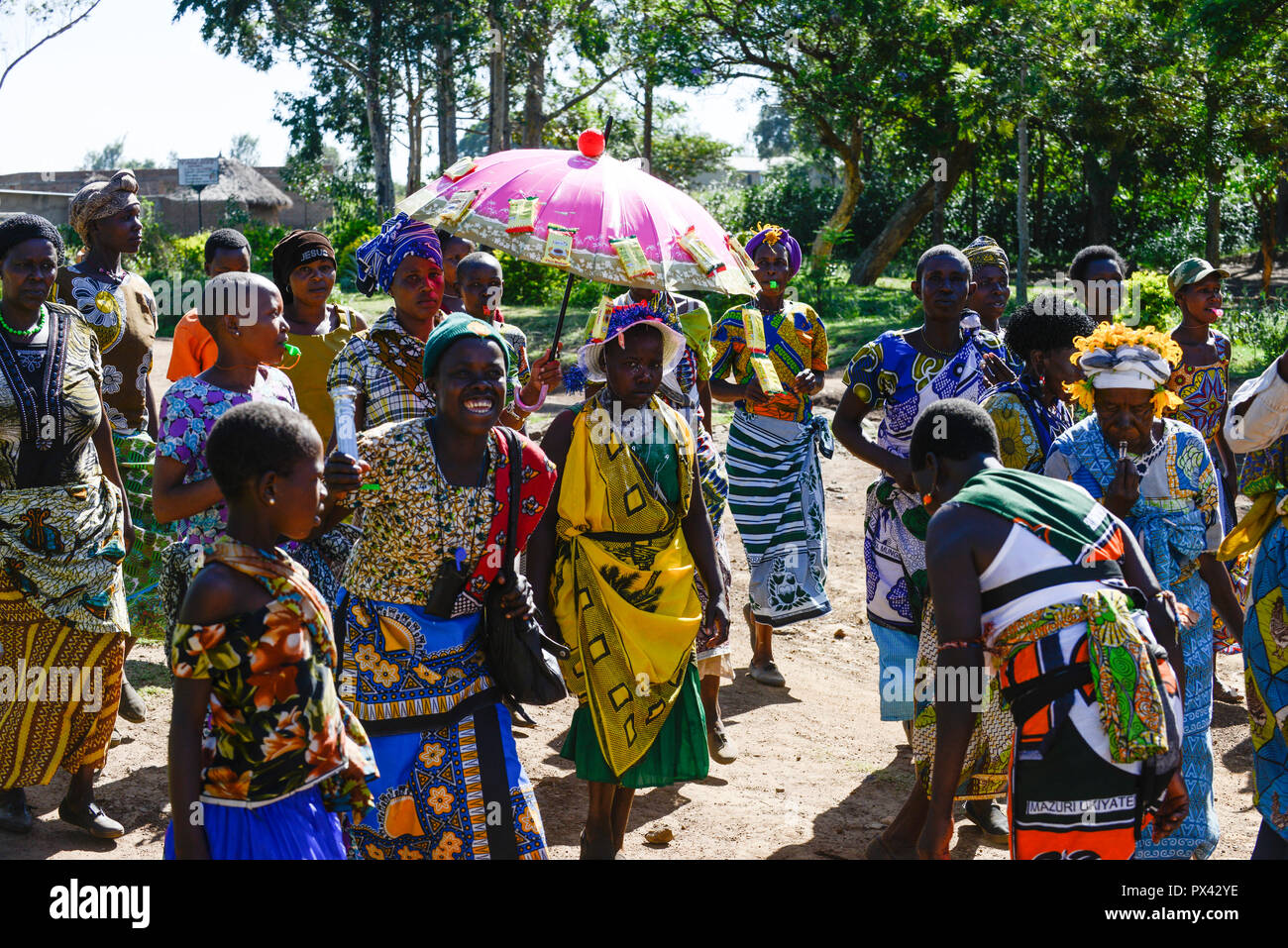 TANZANIA Mara, Tarime, village Masanga, region of the Kuria tribe who practise FGM Female Genital Mutilation, procession from cutting place during cutting season, the girl in yellow cloth under umbrella was circurmcised, published in misso magazine 5/2015 - Stock Image