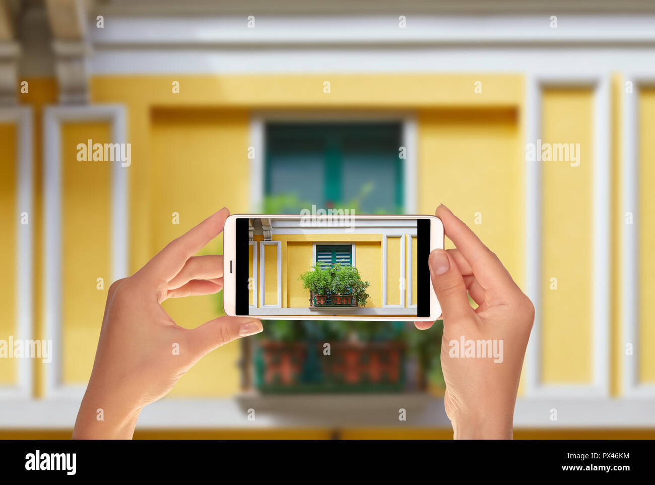 A tourist is taking a photo of the window of one of the houses in the center of Milan is shuttered and decorated with flowers on a mobile phone - Stock Image