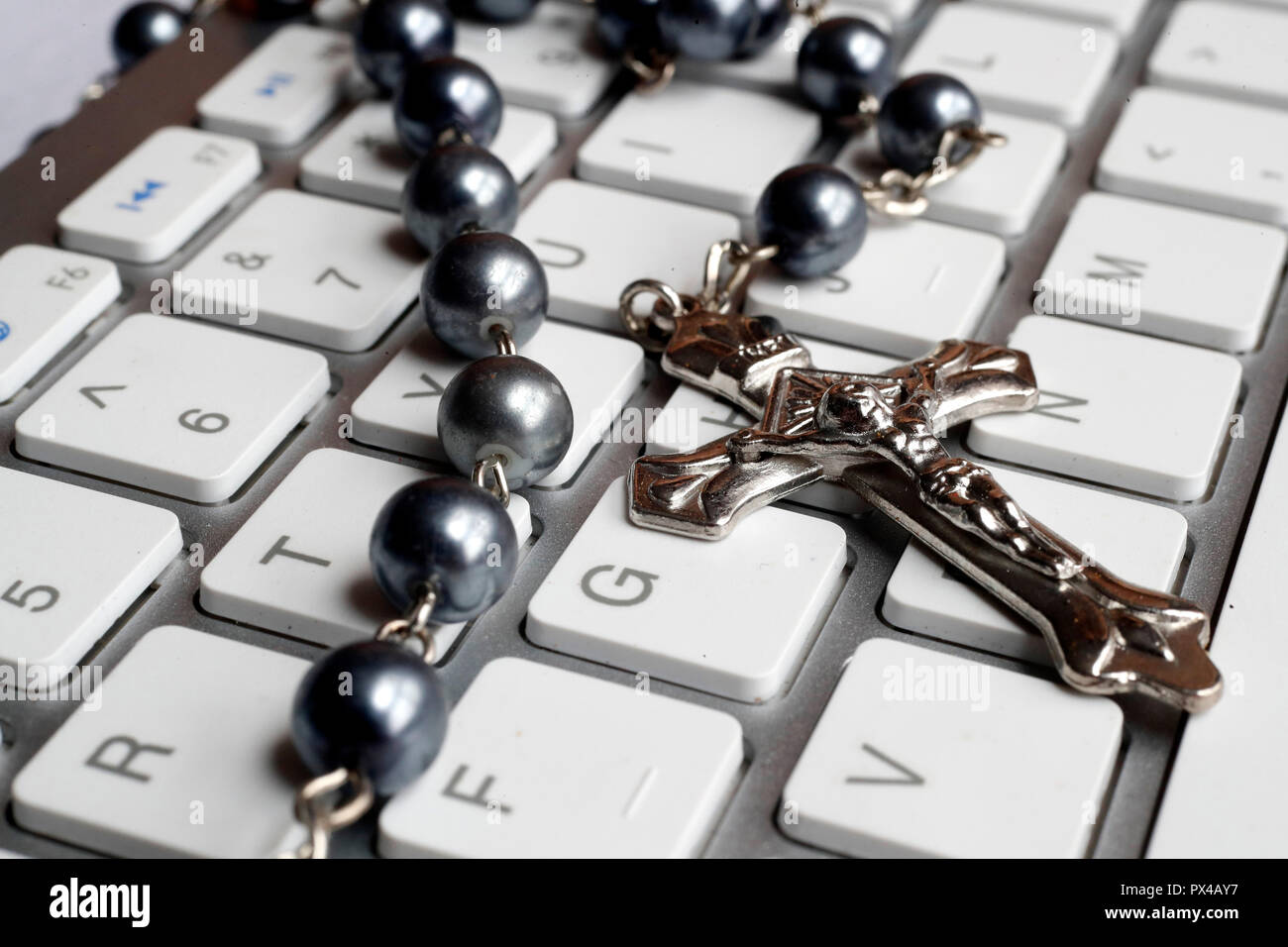 Christian Rosary on a white computer keyboard. - Stock Image