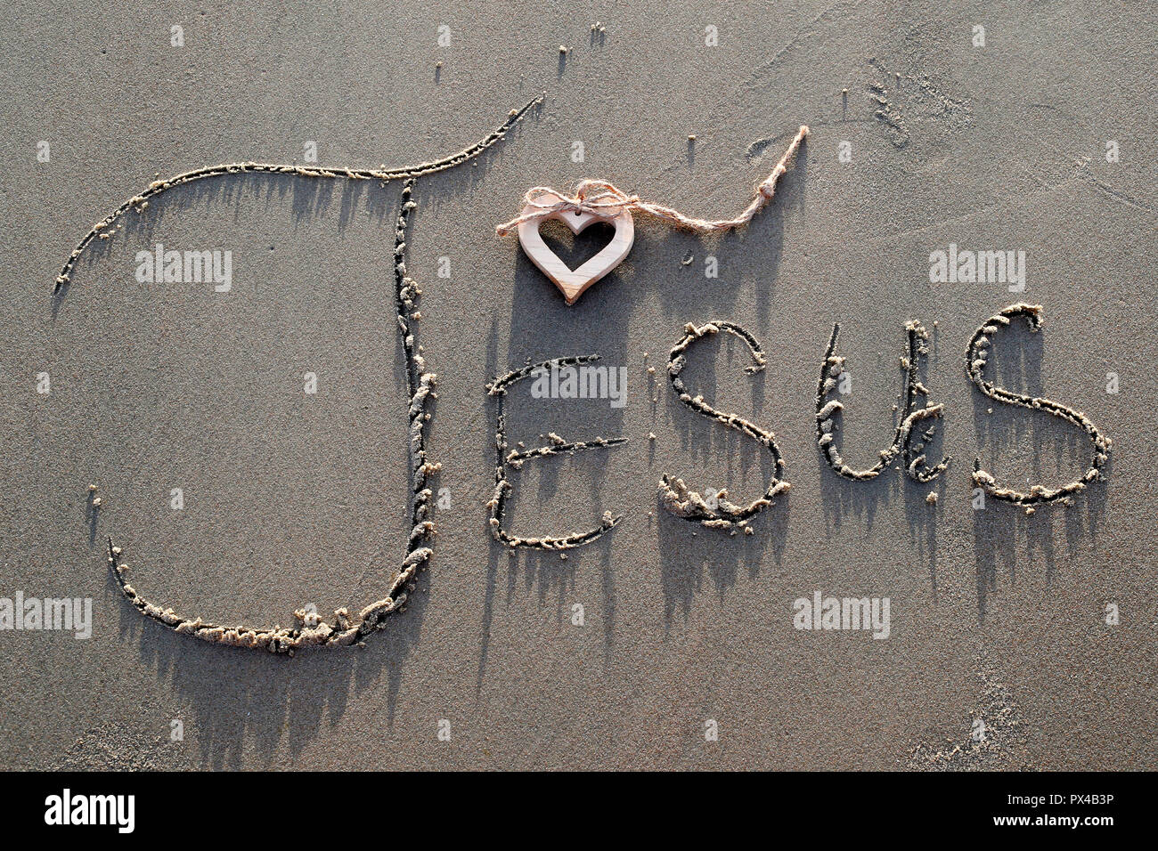 A wooden heart and  the name of Jesus written in the sand. - Stock Image