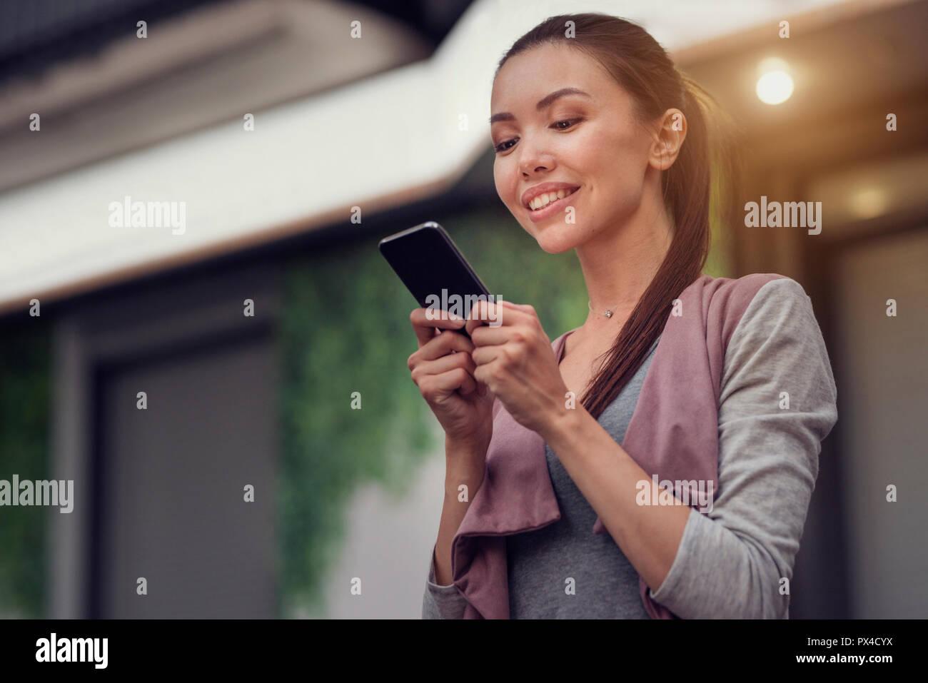 A young beautiful asian woman using an application in her smart phone to read email, send text message, chat, browse or shop online - Stock Image