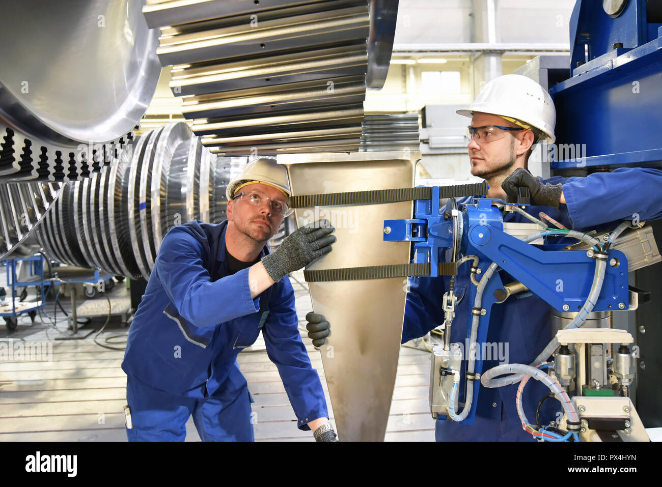 Teamwork - workers manufacturing steam turbines in an industrial factory - Stock Image