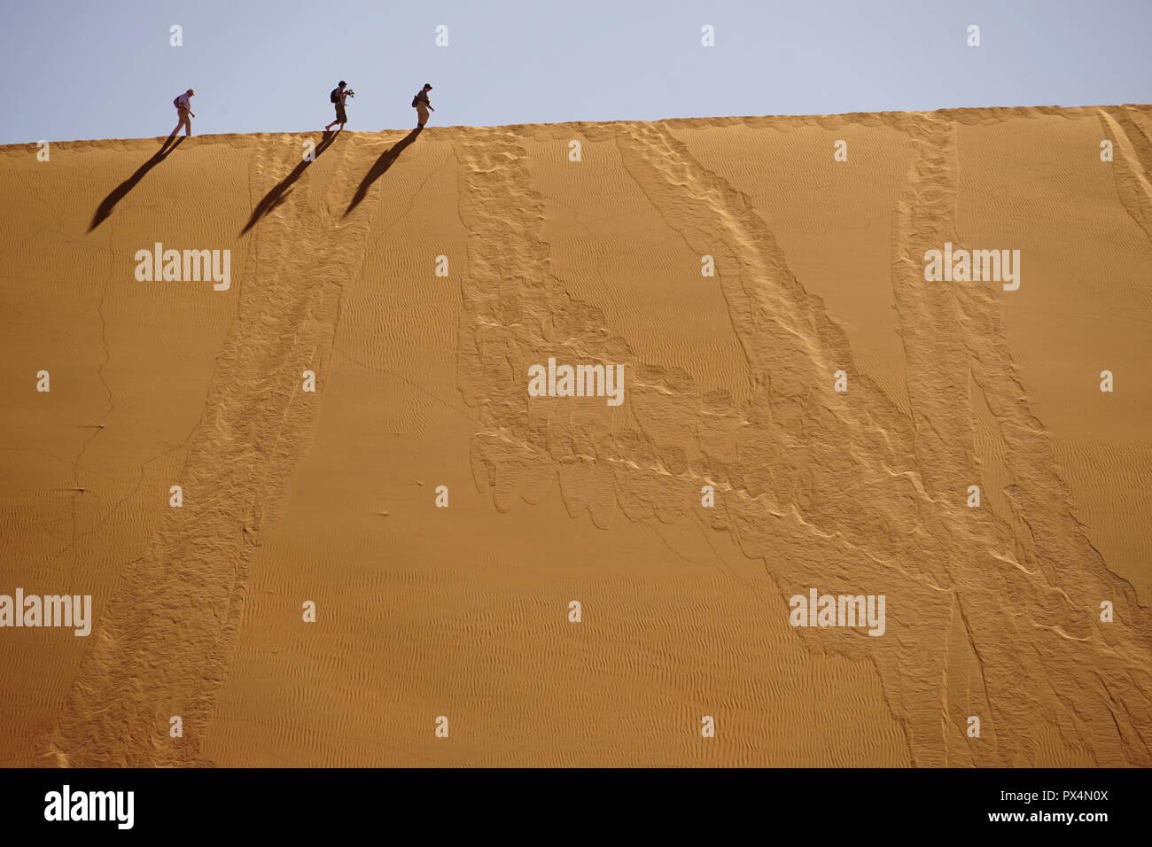 Touristen laufen auf dem Kamm der Düne, Sossusvlei, Namibia, Afrika - Stock Image