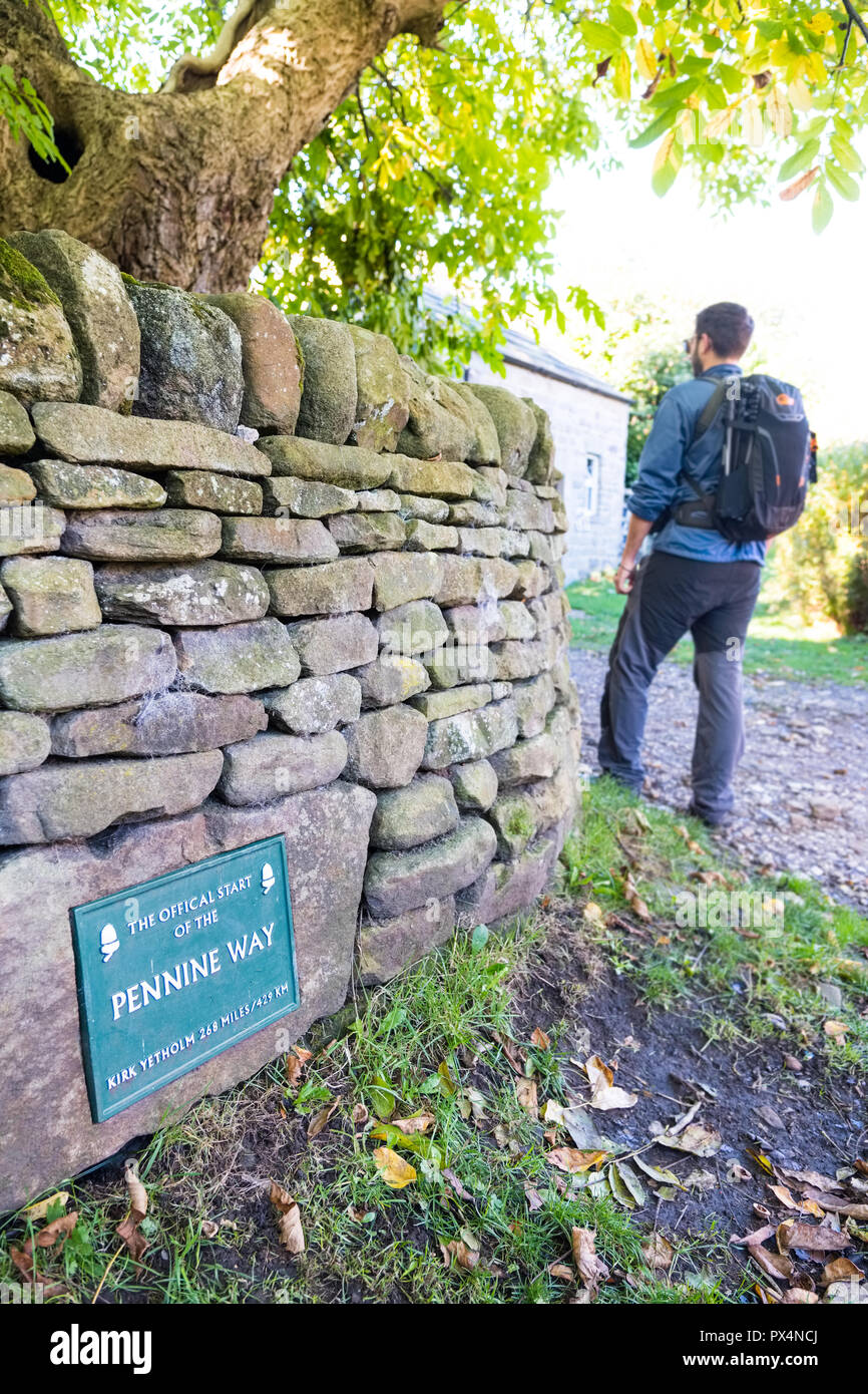 Young man walking past the plaque marking the start of the Pennine Way, Edale, Peak District National Park - Stock Image