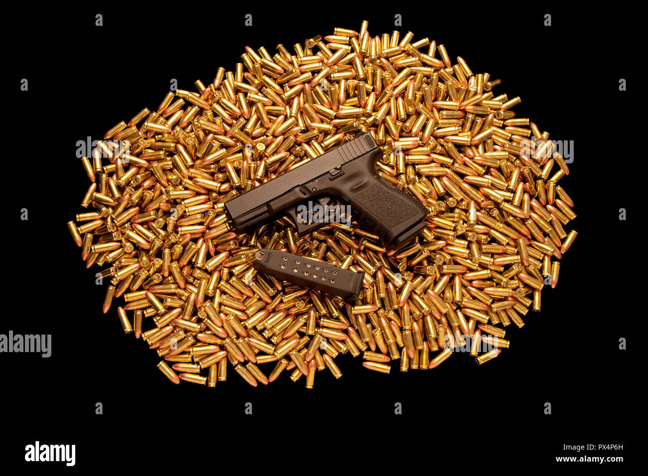 Loaded handgun resting on pile of live ammunition. - Stock Image