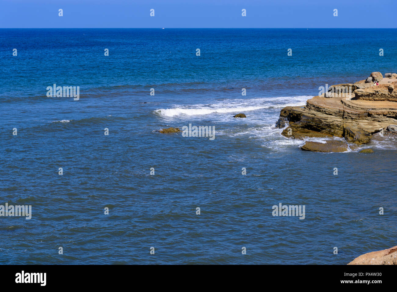 View of ocean and waves crashing onto rocks under a blue sky. - Stock Image