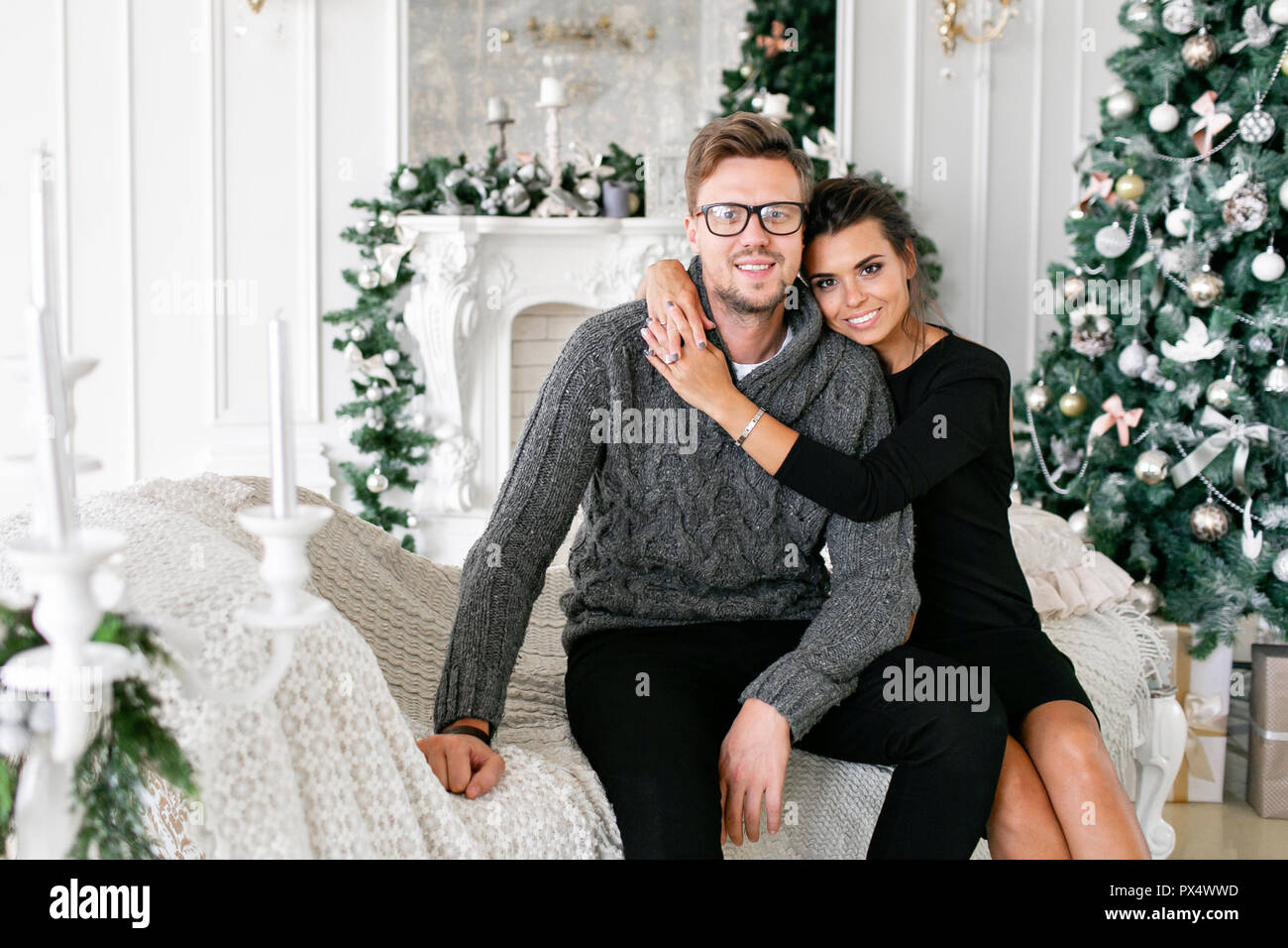 young couple happy family having fun at home christmas morning in bright living room happy new year decorated christmas tree