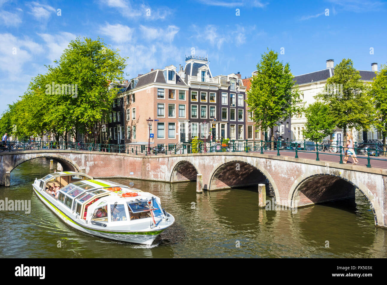 Amsterdam canal boat going under the bridges of Leidsegracht canal at the junction with Keizergracht canal Amsterdam Netherlands Holland EU Europe - Stock Image