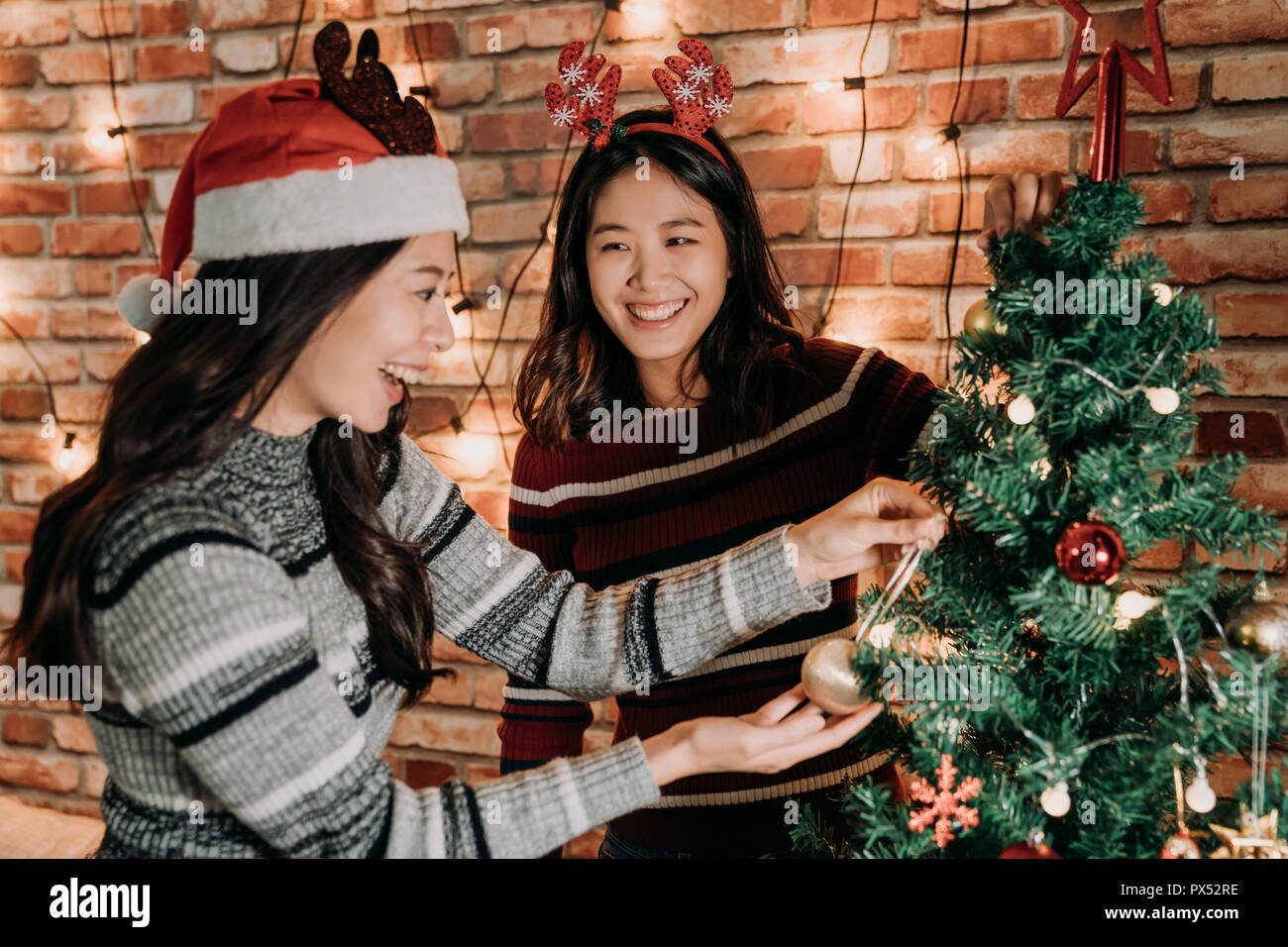 merry xmas and happy new year are coming sisters decorating the christmas tree together at home young girls cheerful preparing for christmas eve con