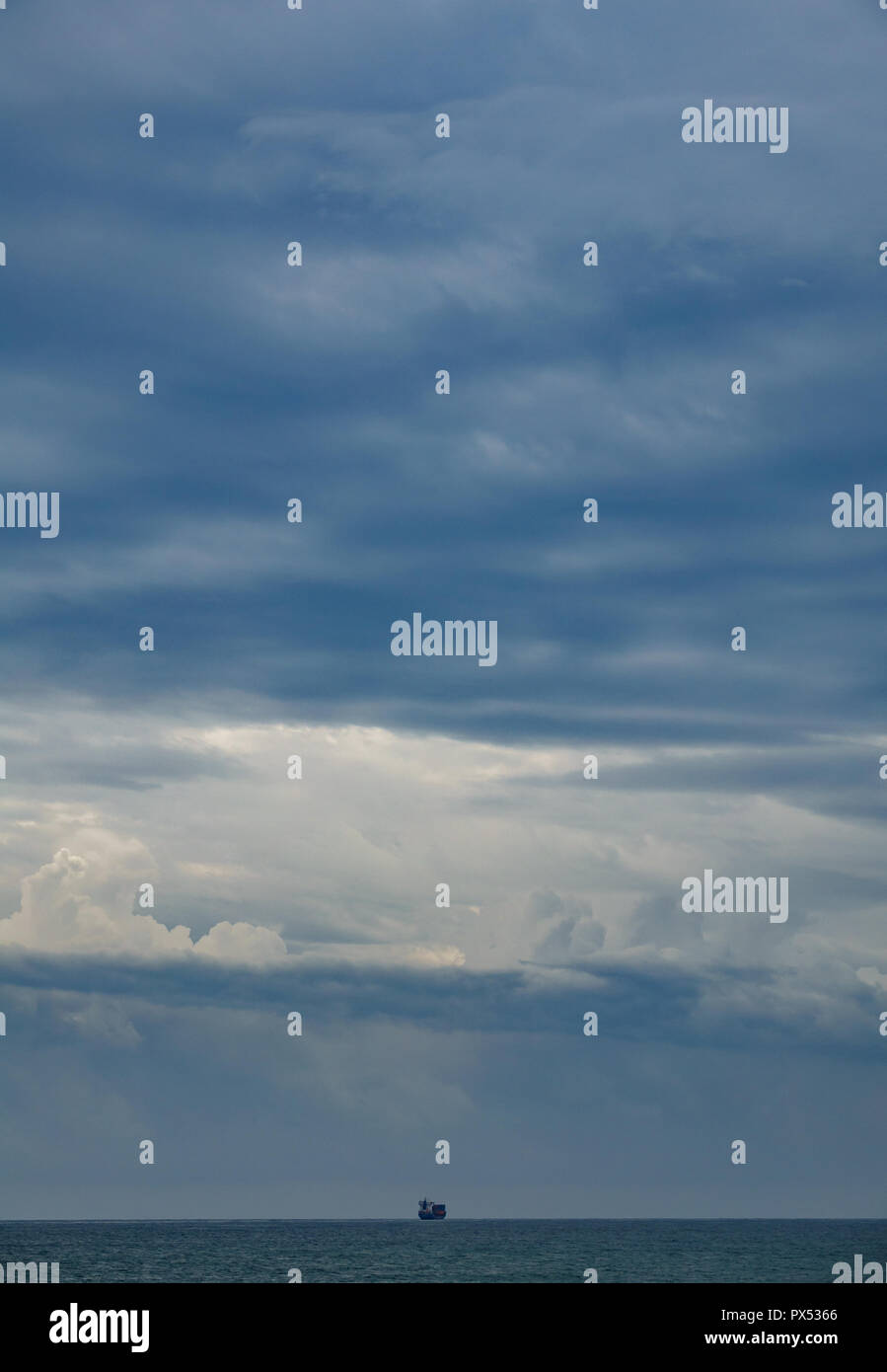 Long shot of cargo ship disappearing in the horizon - Stock Image