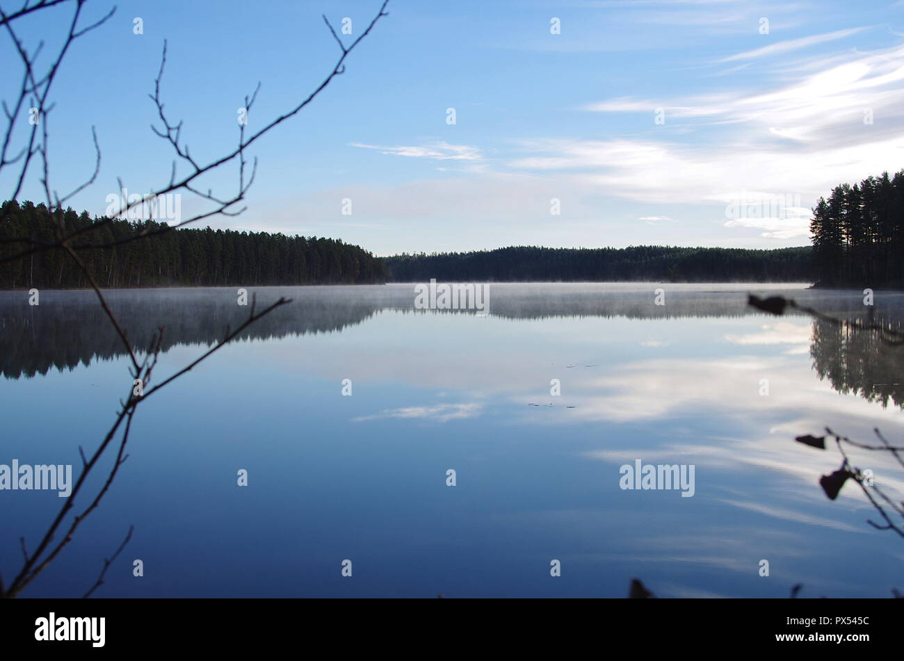 Morning mist over a lake in Dalarna on a cold autumn morning. - Stock Image