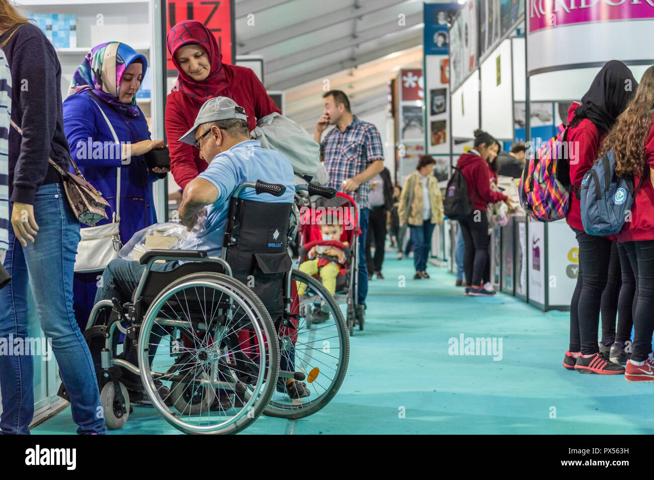 Eskisehir, Turkey - October 09, 2018: Man in wheelchair visiting Eskisehir Book Fair with his family - Stock Image