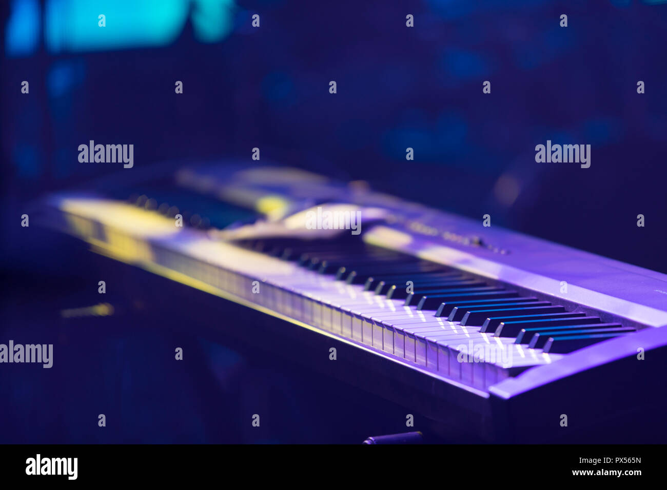A synthesizer illuminated by stage lights - Stock Image