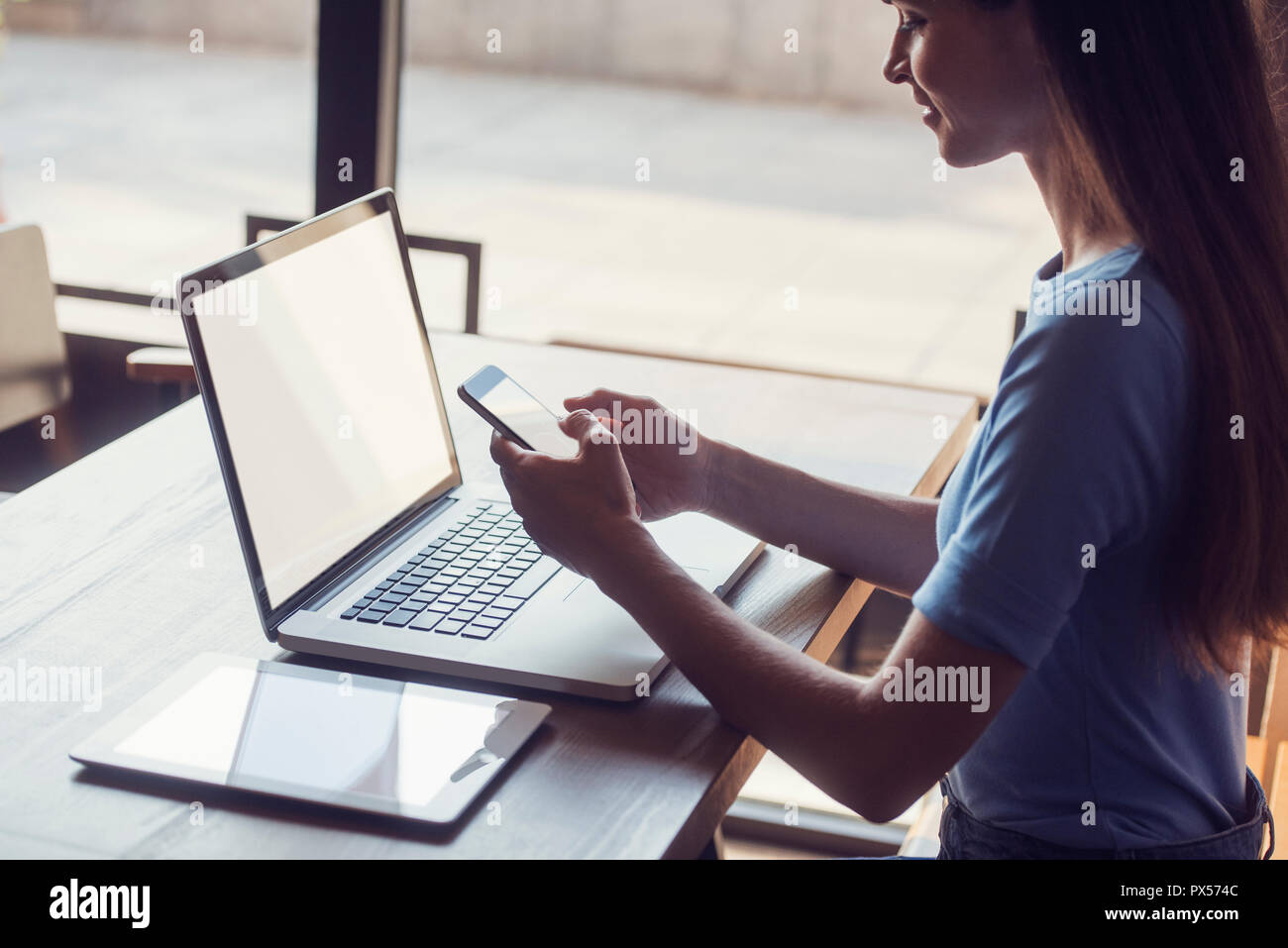 close up multitasking woman using tablet, laptop and cellphone, with blank screens, indoors on a table - Stock Image