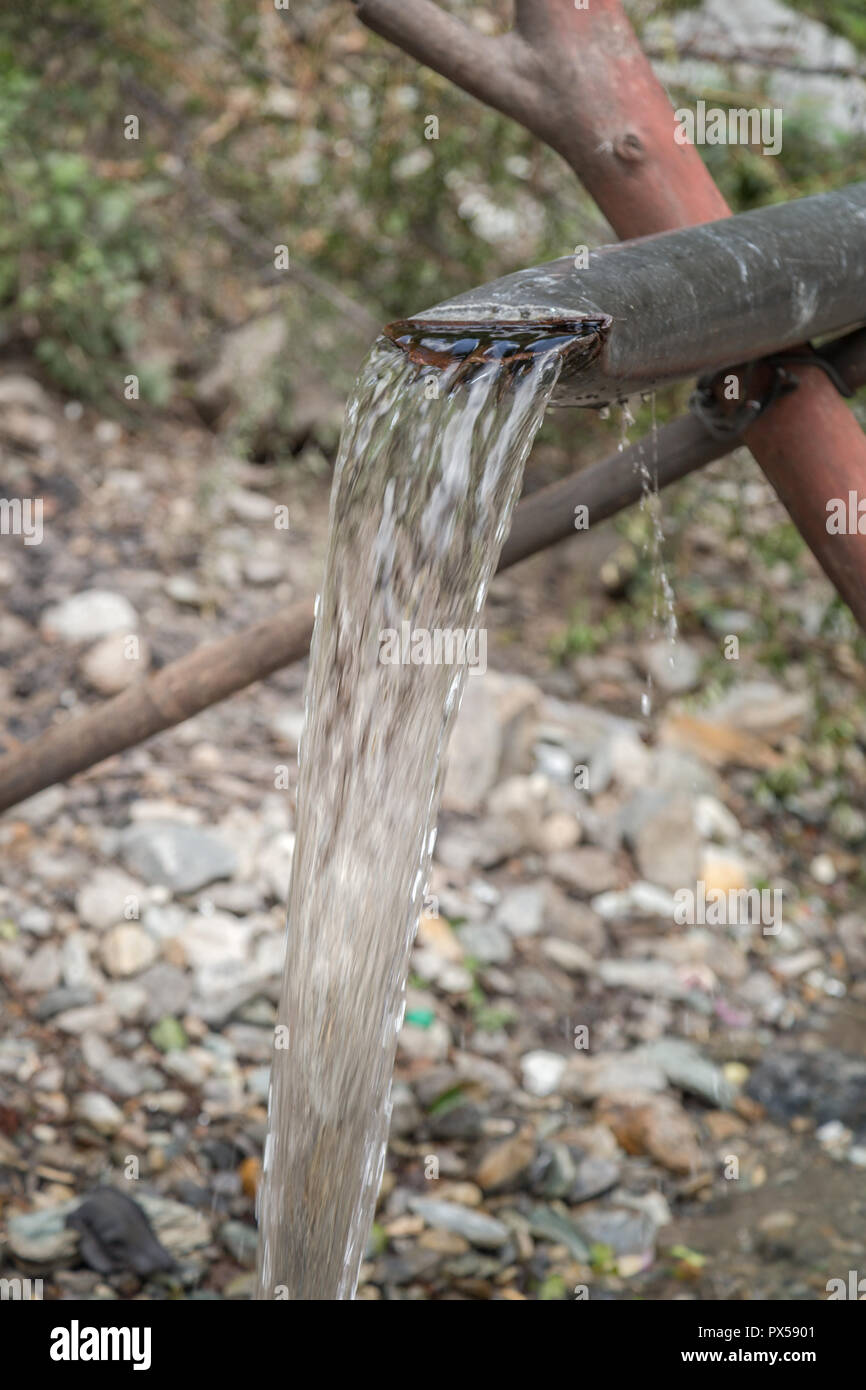 Spring Water Comes Out Of steel pipe in hilly area of uttarakhand - Stock Image