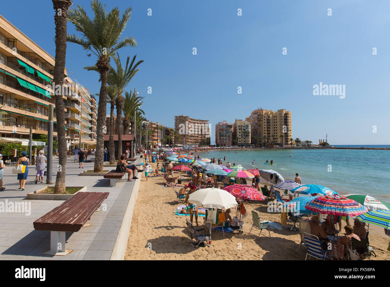 Torrevieja Spain beautiful October sunshine and hot weather made tourists and visitors put up parasols and umbrellas - Stock Image
