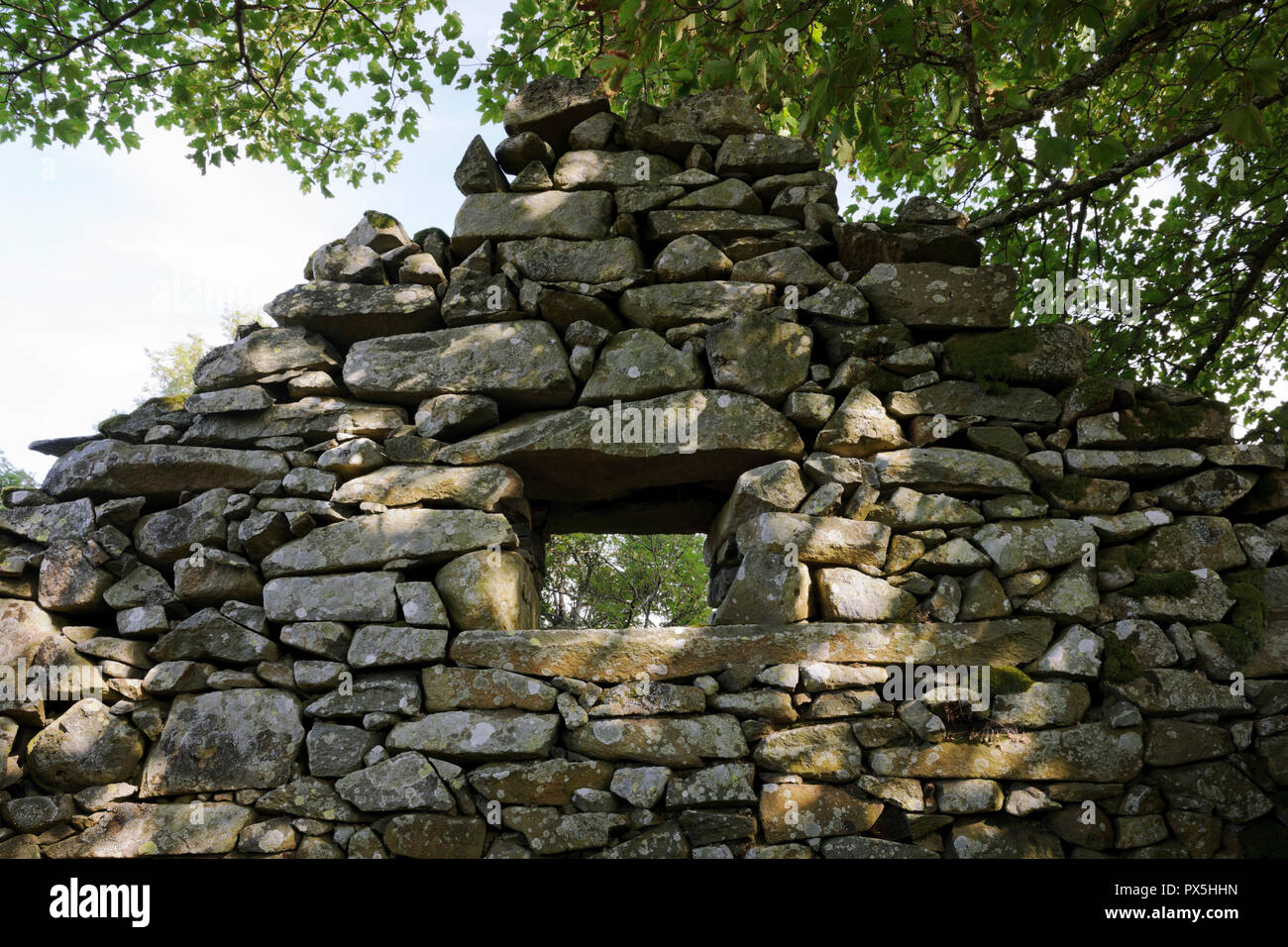 Looking from the inside to a window in a gable wall of a drystone built barn at the abandoned upland farmstead of Hafod y Garreg, Conwy Valley, Wales. - Stock Image