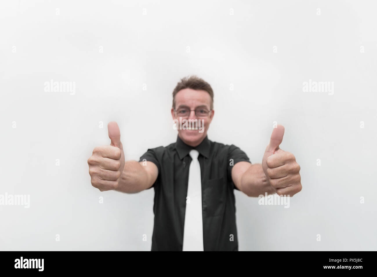 thumbs up business man in optimism pose in success concept with a big smile white teeth gesture - Stock Image