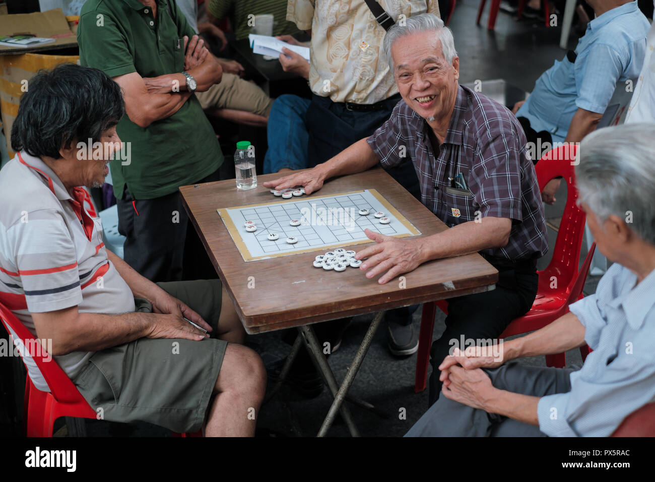 Ethnic Chinese citizens in playing Chinese versions of chess behind the Buddha Tooth Relic Temple and Museum, Telok Ayer Square, Chinatown, Singapore - Stock Image