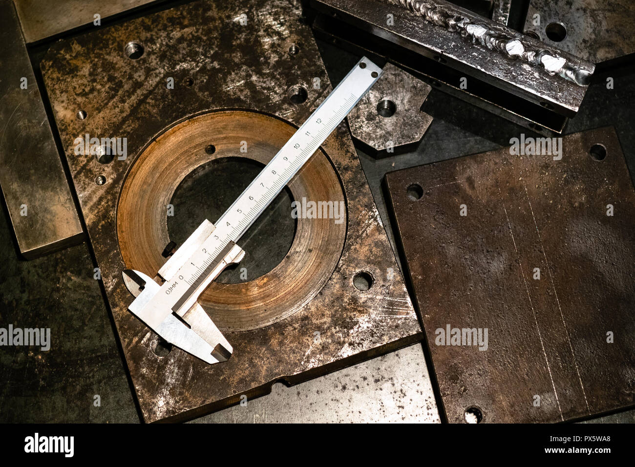 Metalworking still life - top view of callipers on metal workbench in turnery workshop in warm yellow light - Stock Image