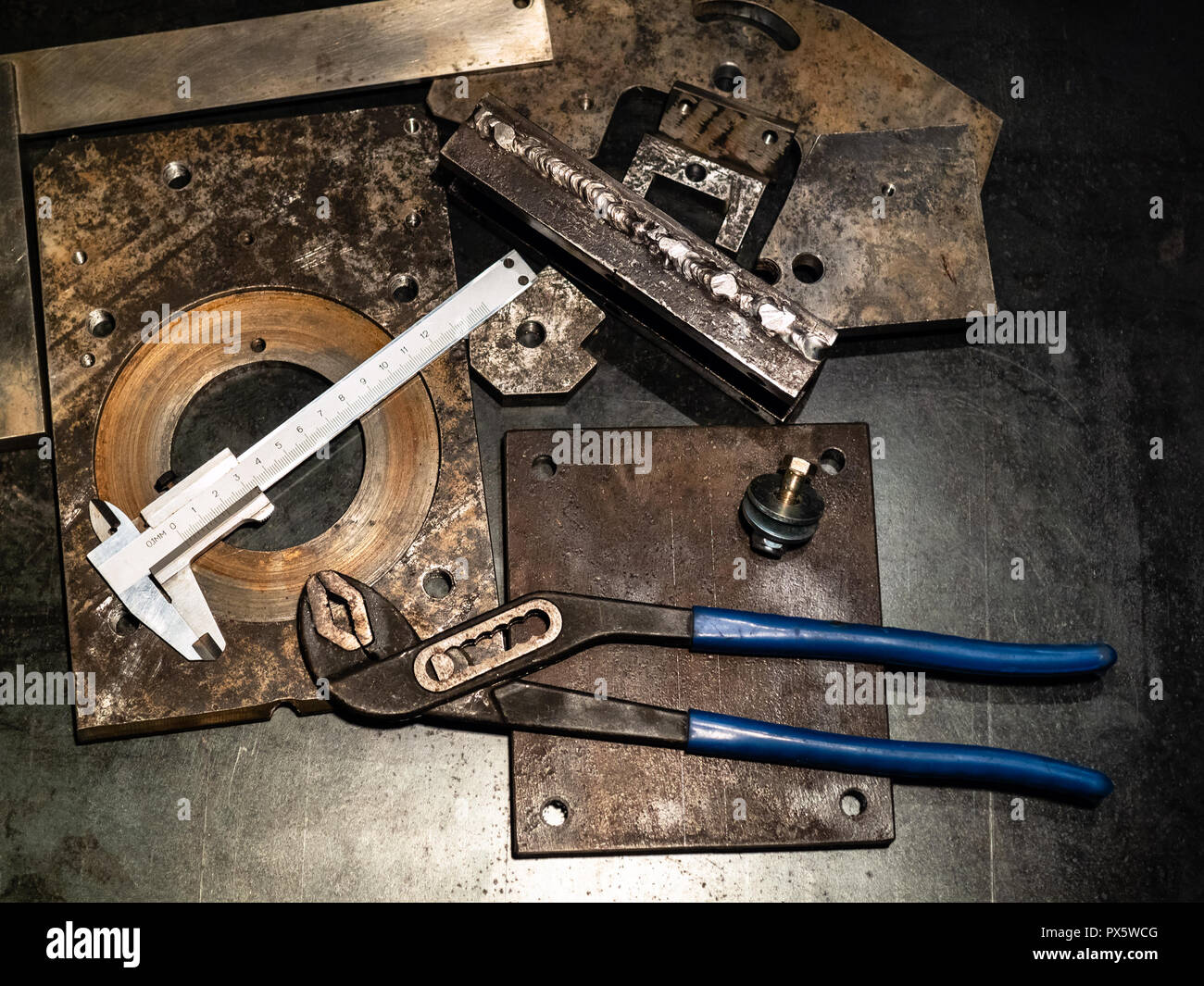 Metalworking still life - top view of callipers and adjustable pliers on metal workbench in turnery workshop in warm yellow light - Stock Image