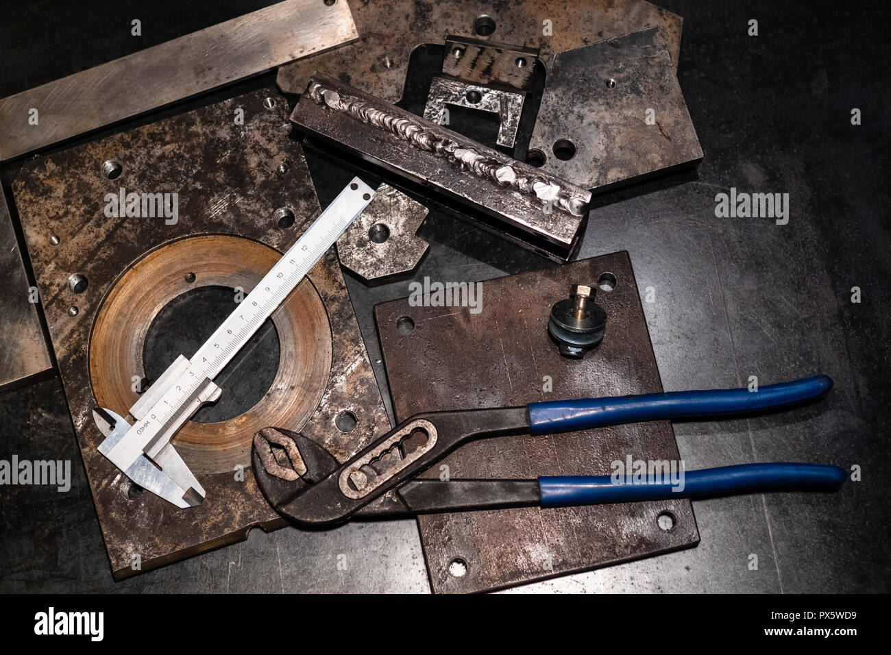 Metalworking still life - top view of calipers and adjustable pliers on metal workbench in turnery workshop in cold blue light - Stock Image