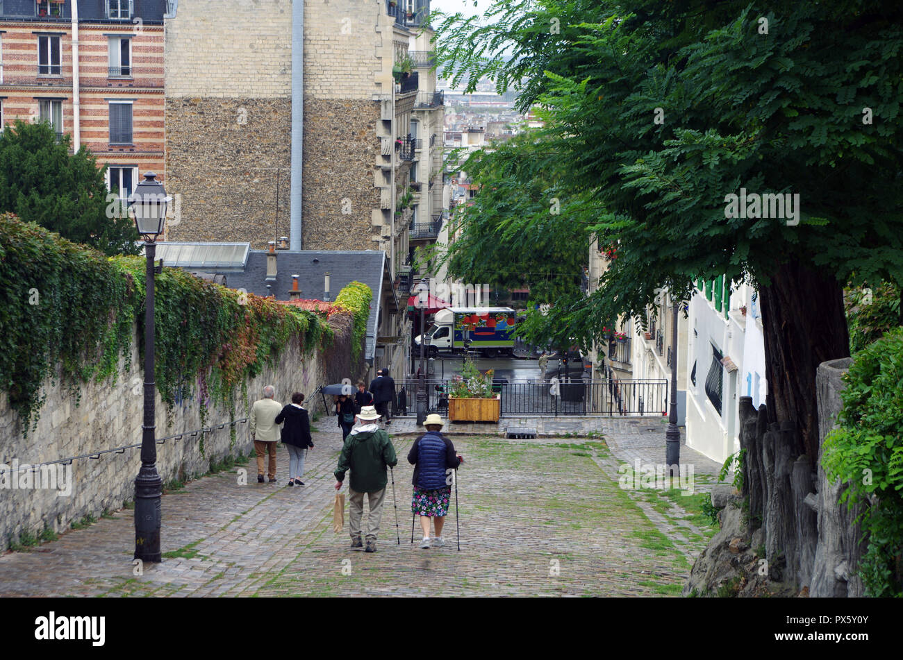 Couple of tourists or Parisians walking in the cobbled streets of Paris - Stock Image