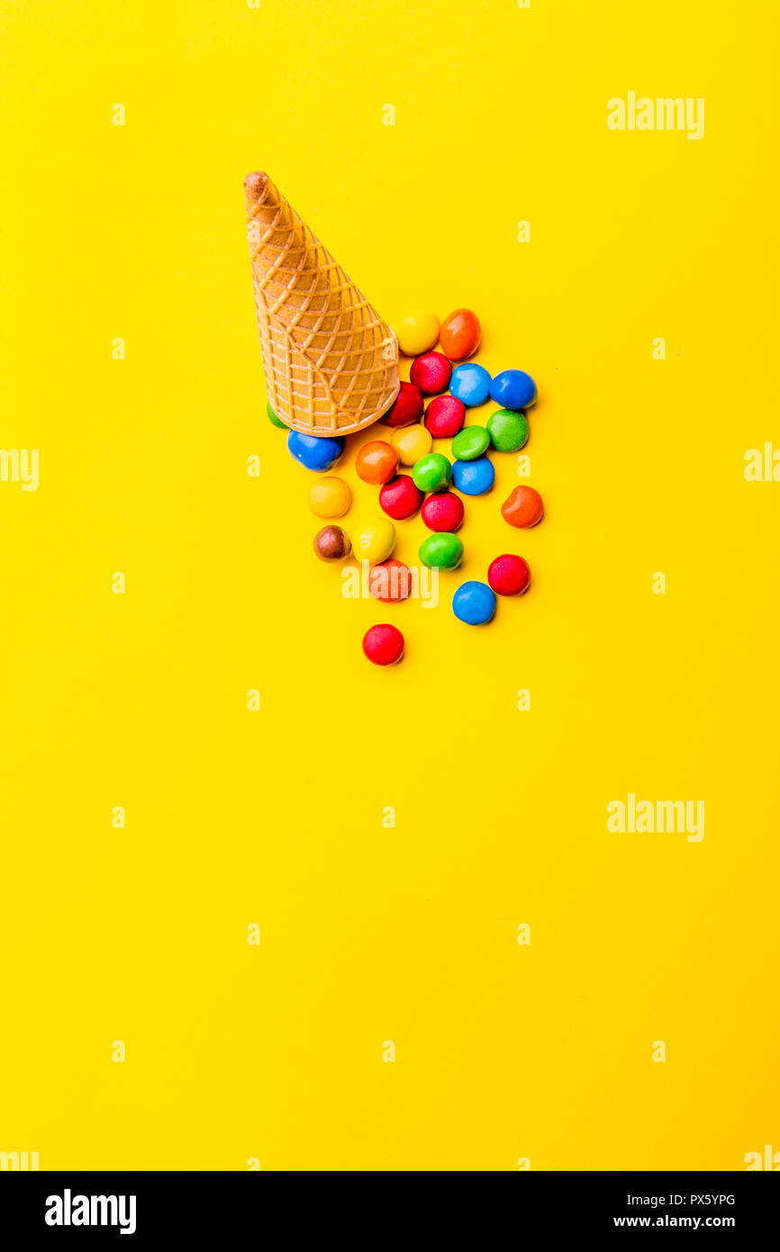 Ice creame cone with candy on yellow background. Minimalistic concept - Stock Image