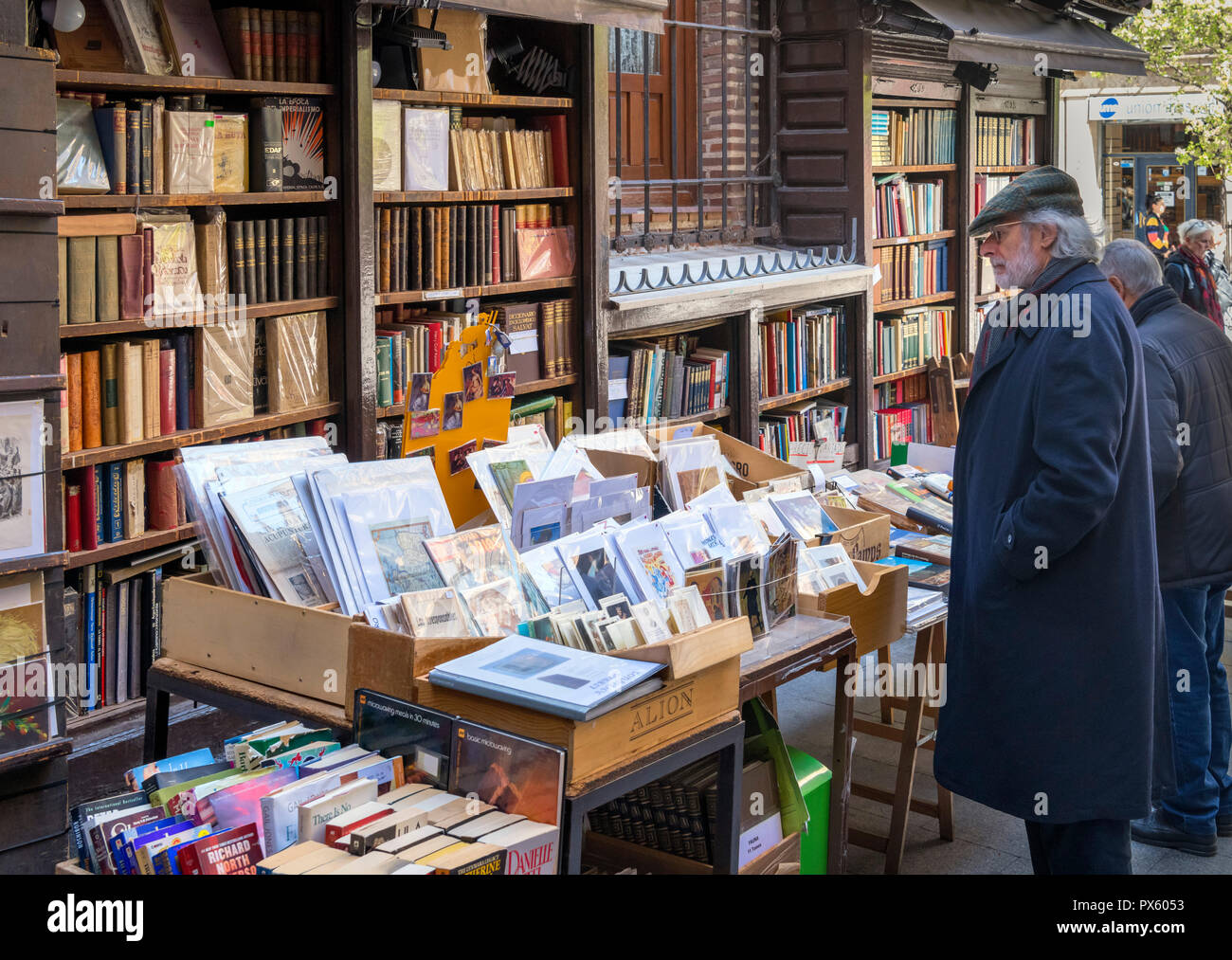 Man browsing books on a stall selling second hand books and art prints, Calle del Arenal, Madrid, Spain - Stock Image