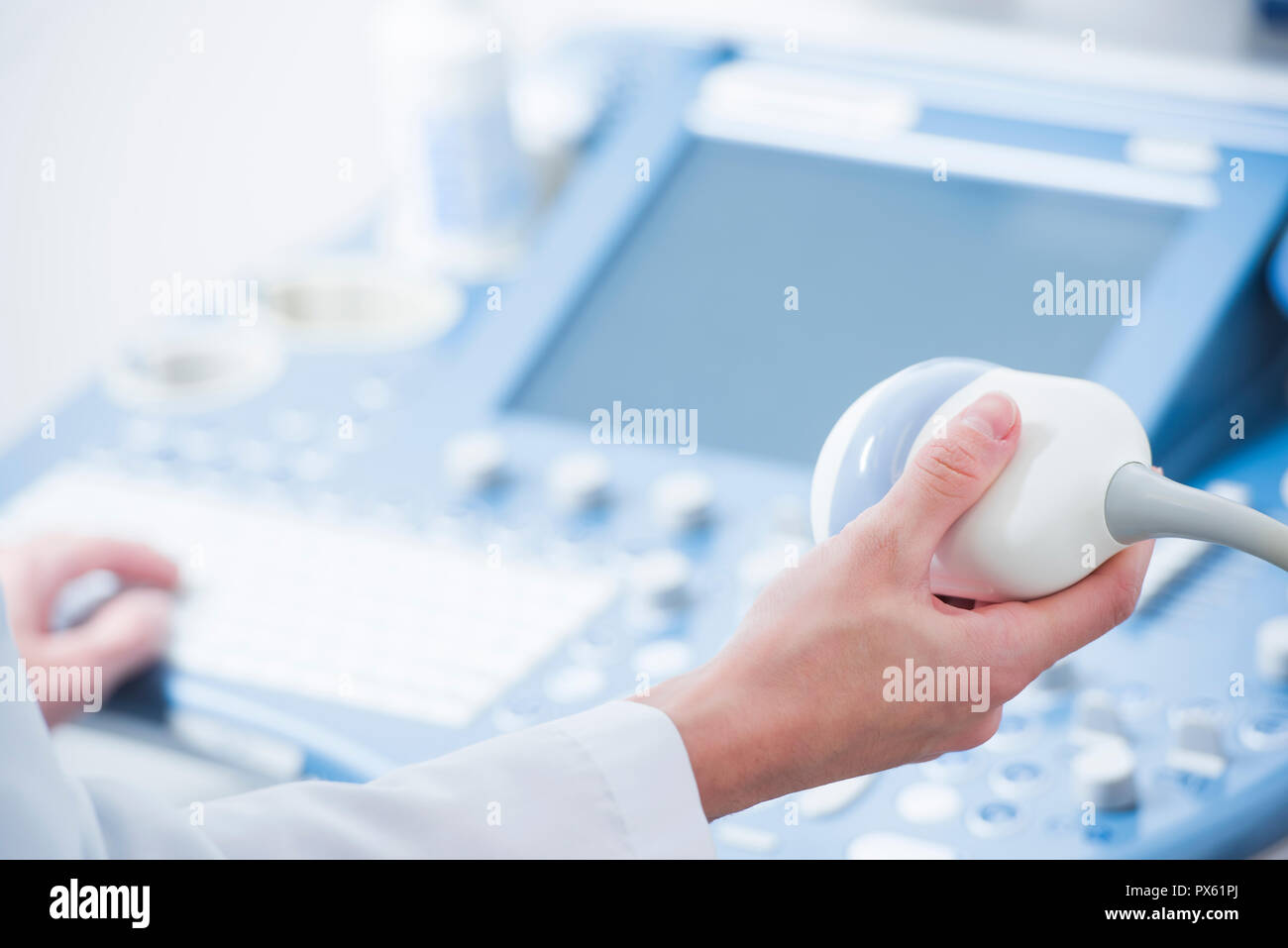 young woman doctor's hands close up preparing for an ultrasound device scan. - Stock Image