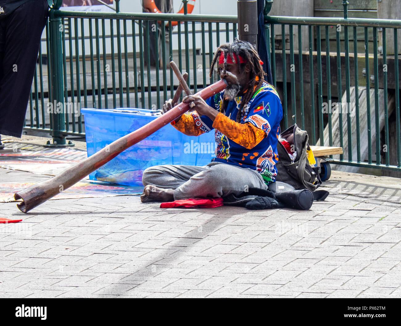 Indigenous aboriginal man playing the didgeridoo musical instrument in Circular Quay Sydney NSW Australia. - Stock Image