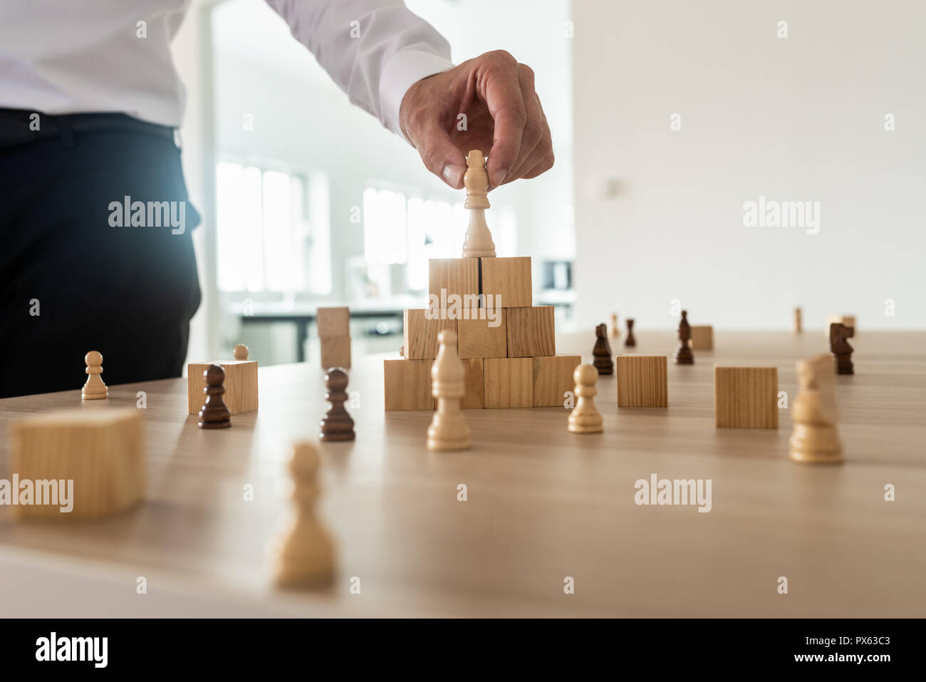 Business hierarchy concept with businessman placing chess figure of king on top of wooden stacked wooden blocks and other figures spread on office des - Stock Image