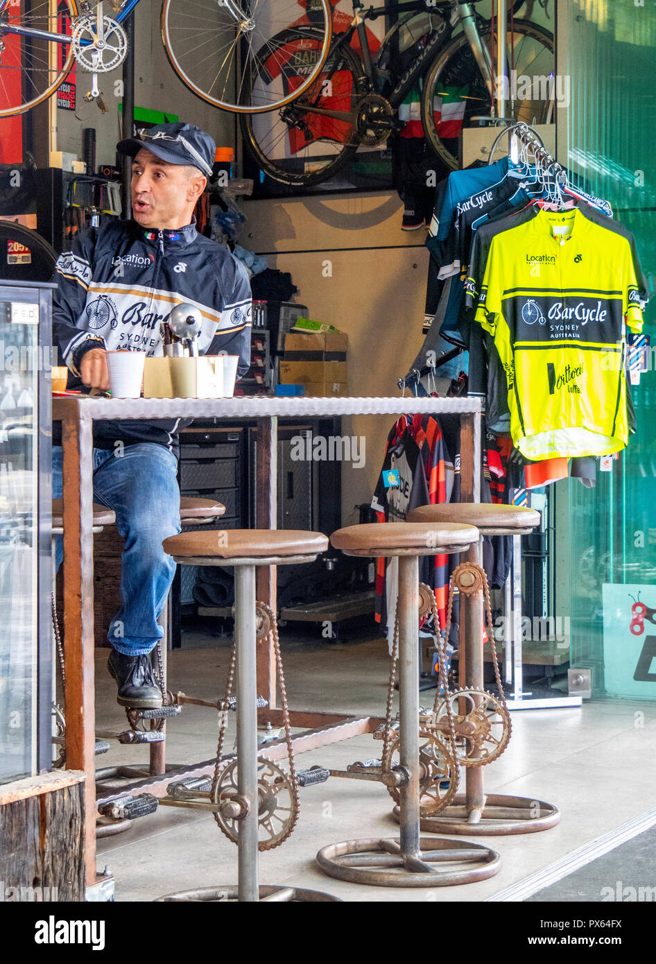 Outstanding Man Having A Coffee In A Cafe Bicycle Shop With Bar Stools Evergreenethics Interior Chair Design Evergreenethicsorg