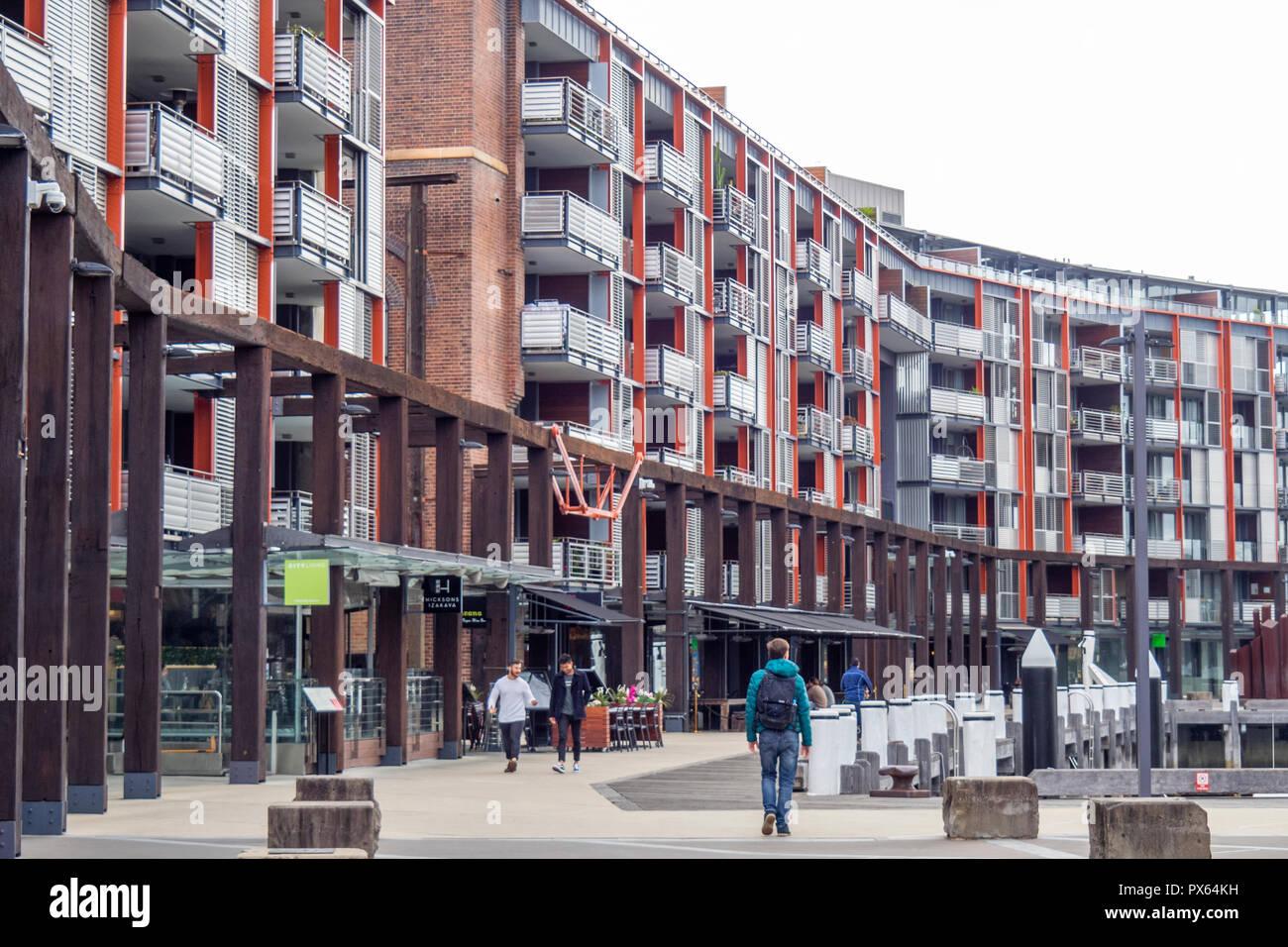 Pedestrians walking along the boardwalk in high density residential development in Walsh Bay Sydney NSW Australia. - Stock Image